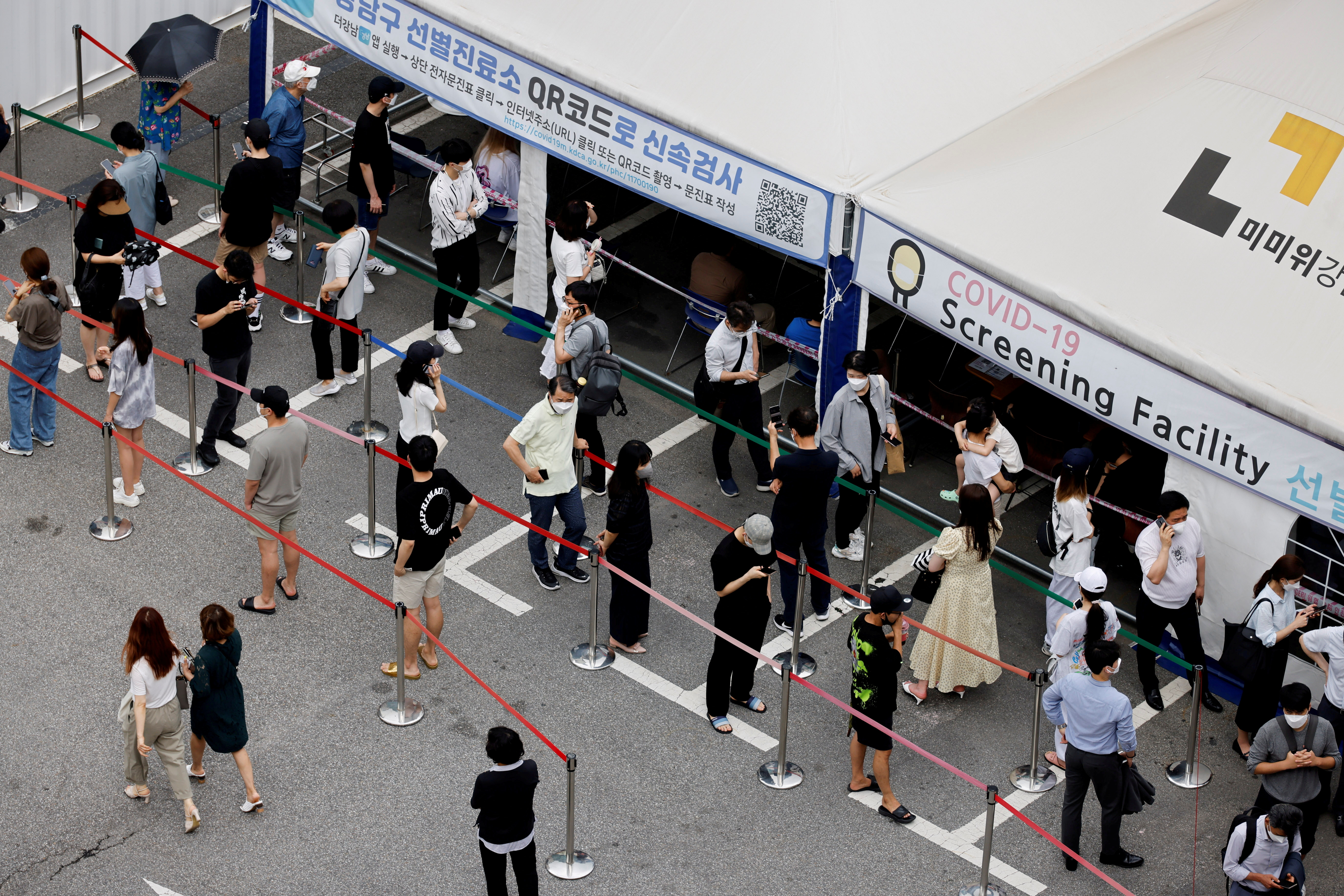 People wait in line for a coronavirus disease (COVID-19) test at a testing site which is temporarily set up at a public health center in Seoul, South Korea, July 9, 2021.  REUTERS/ Heo Ran/File Photo