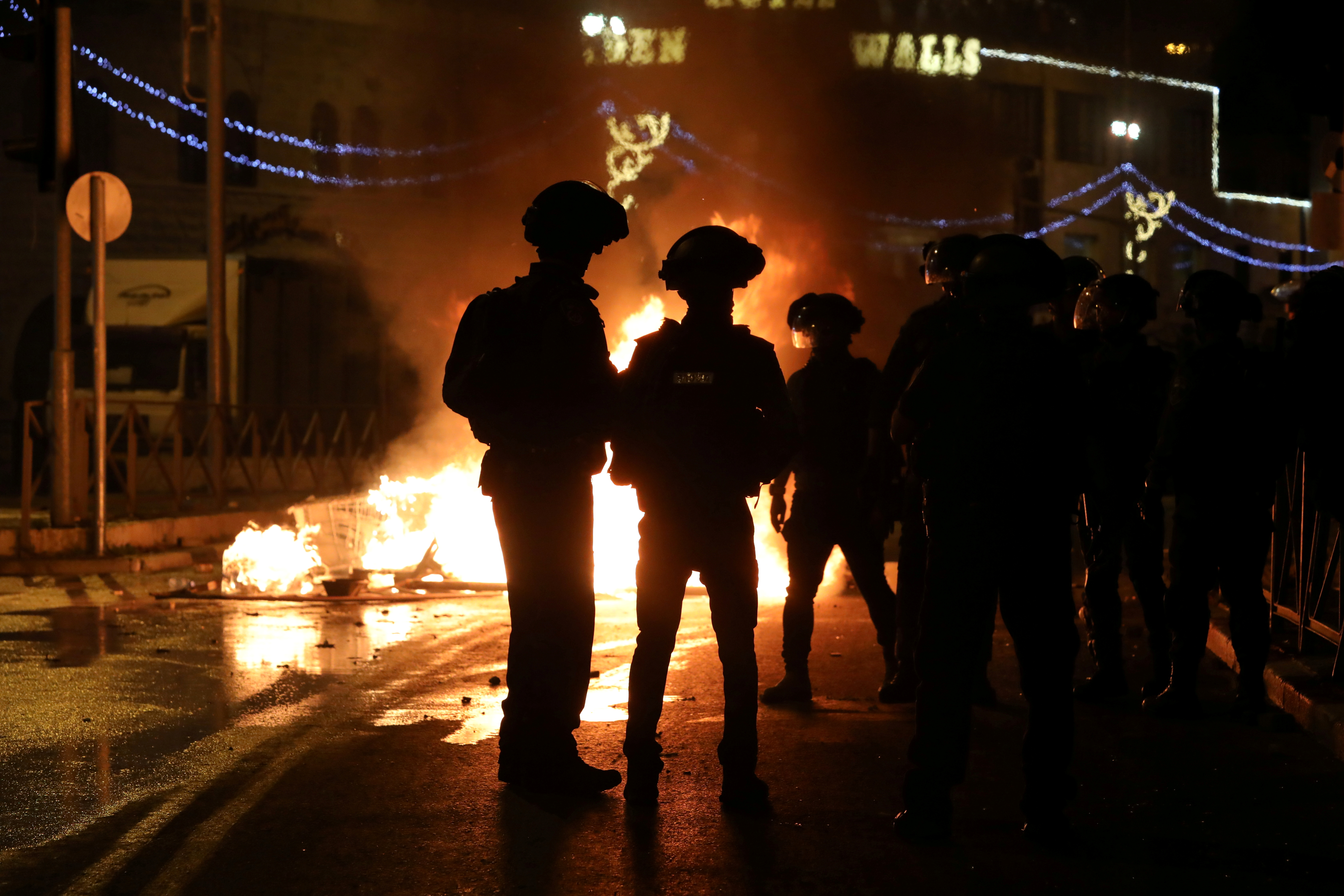 Israeli police officers stand next to a burning barricade during clashes with Palestinians, as the Muslim holy fasting month of Ramadan continues, in Jerusalem, April 22, 2021. REUTERS/Ammar Awad