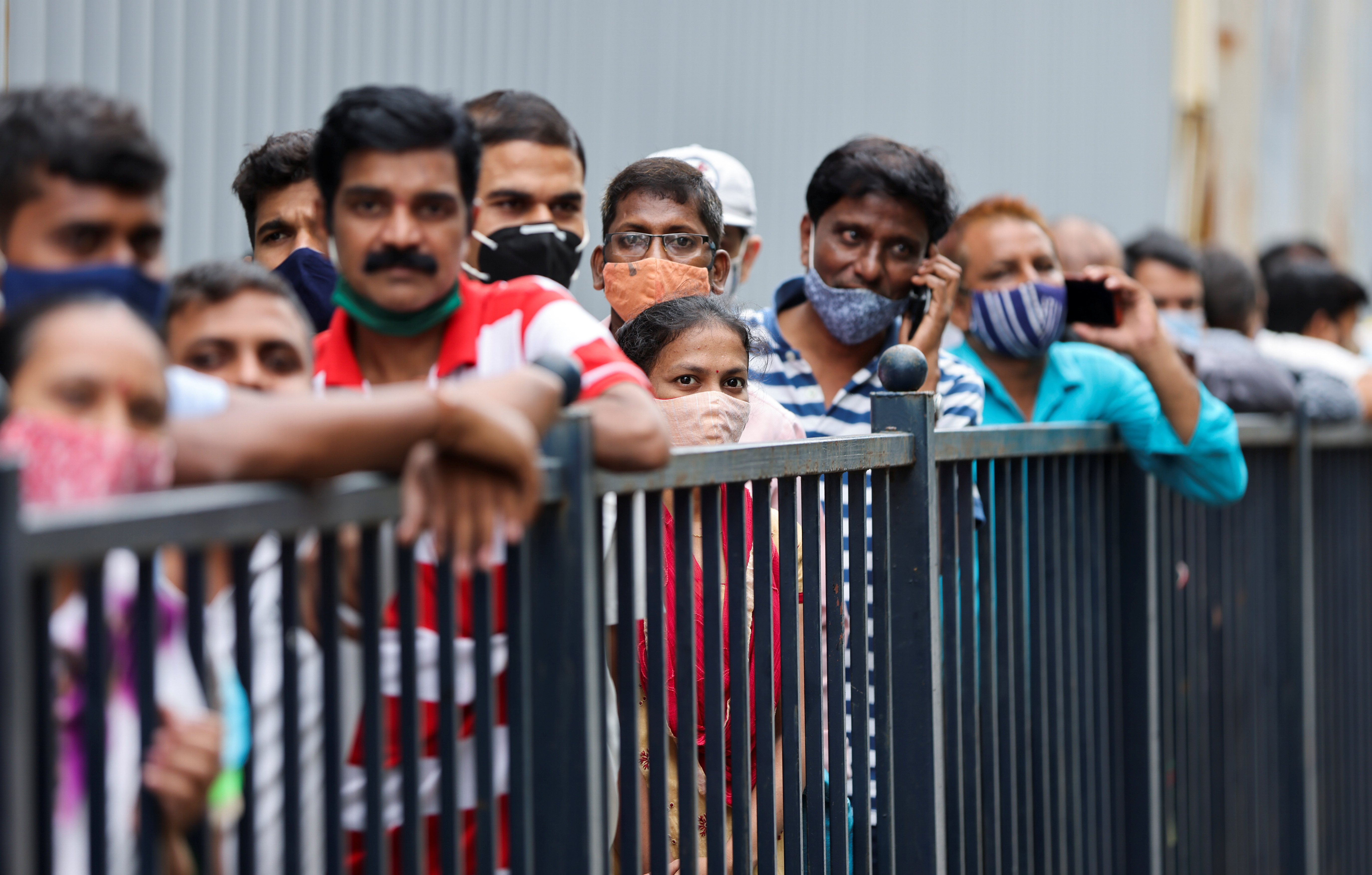 People wait in a queue to receive the vaccine against coronavirus disease (COVID-19) outside a cinema hall in Mumbai, India, August 17, 2021. REUTERS/Francis Mascarenhas