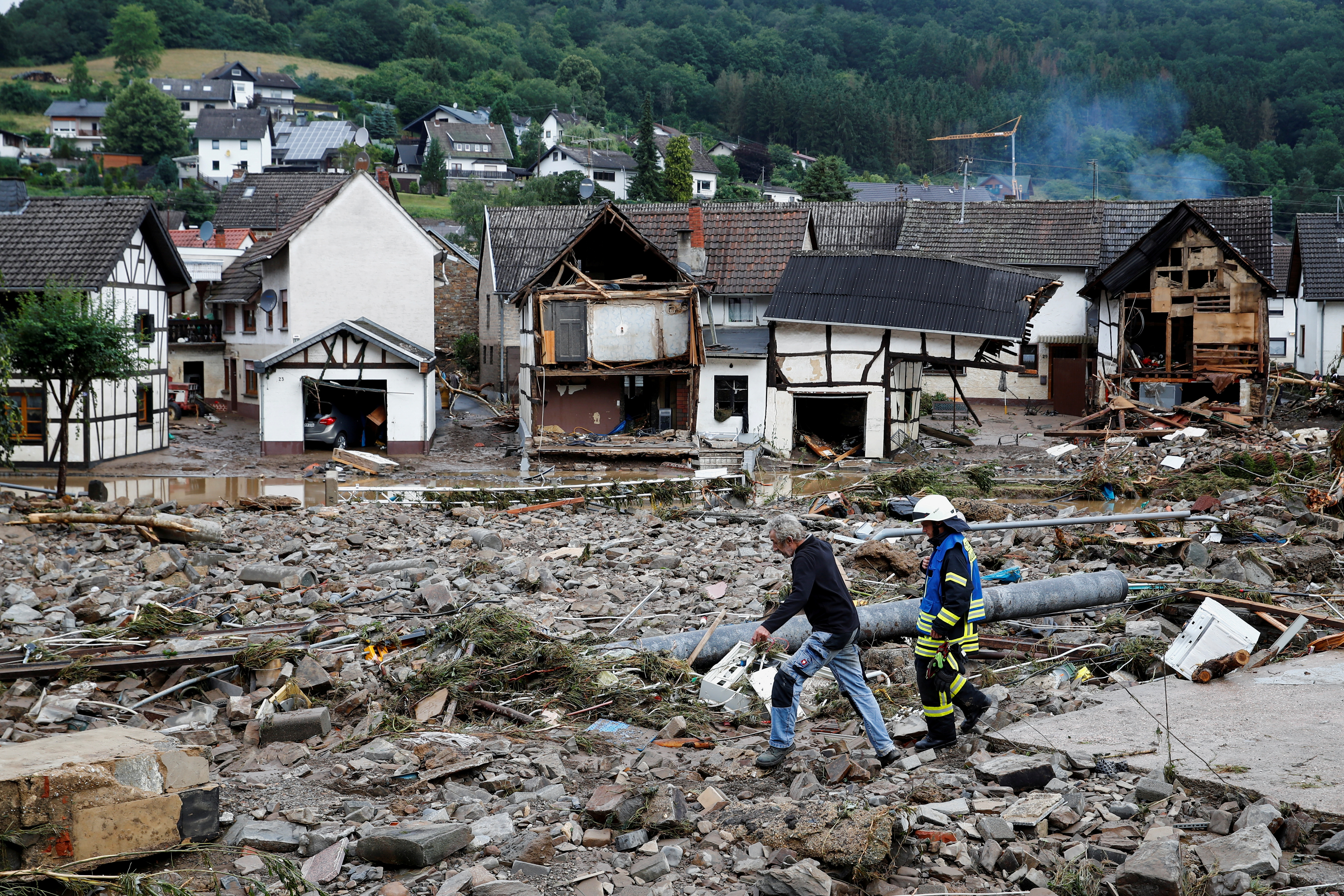 A man and firefighter walk through debris, following heavy rainfalls in Schuld, Germany, July 15, 2021. REUTERS/Wolfgang Rattay