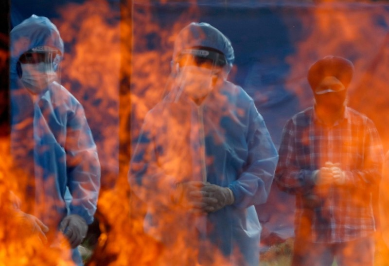 Relatives stand next to the burning pyre of a man who died from the coronavirus disease (COVID-19) during his cremation at a crematorium ground in Srinagar May 25, 2021. REUTERS/Danish Ismail