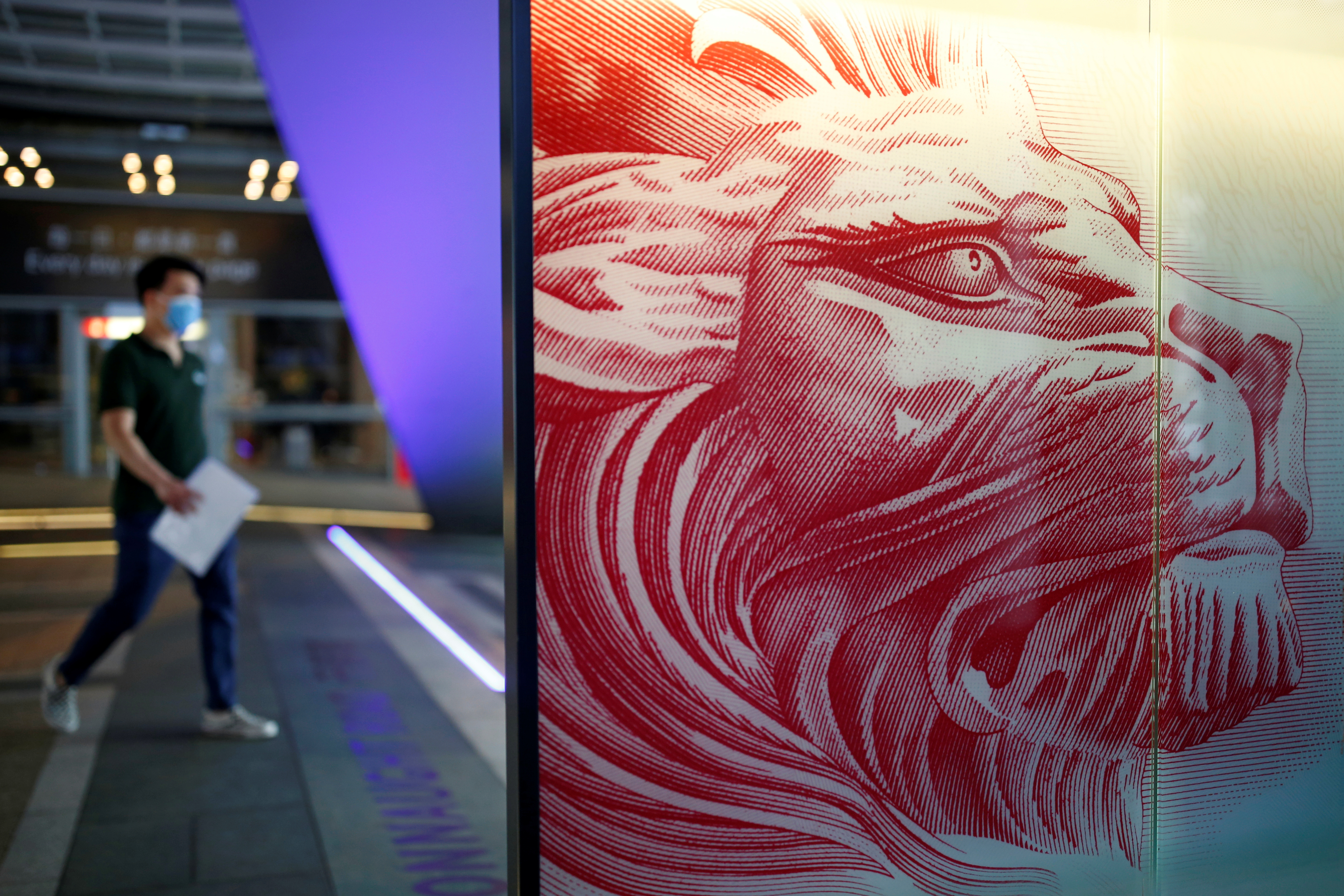 A pedestrian walks past a panel showing the HSBC lion at its headquarters at the financial Central district in Hong Kong, China August 4, 2020. REUTERS/Tyrone Siu - RC207I96XPCZ