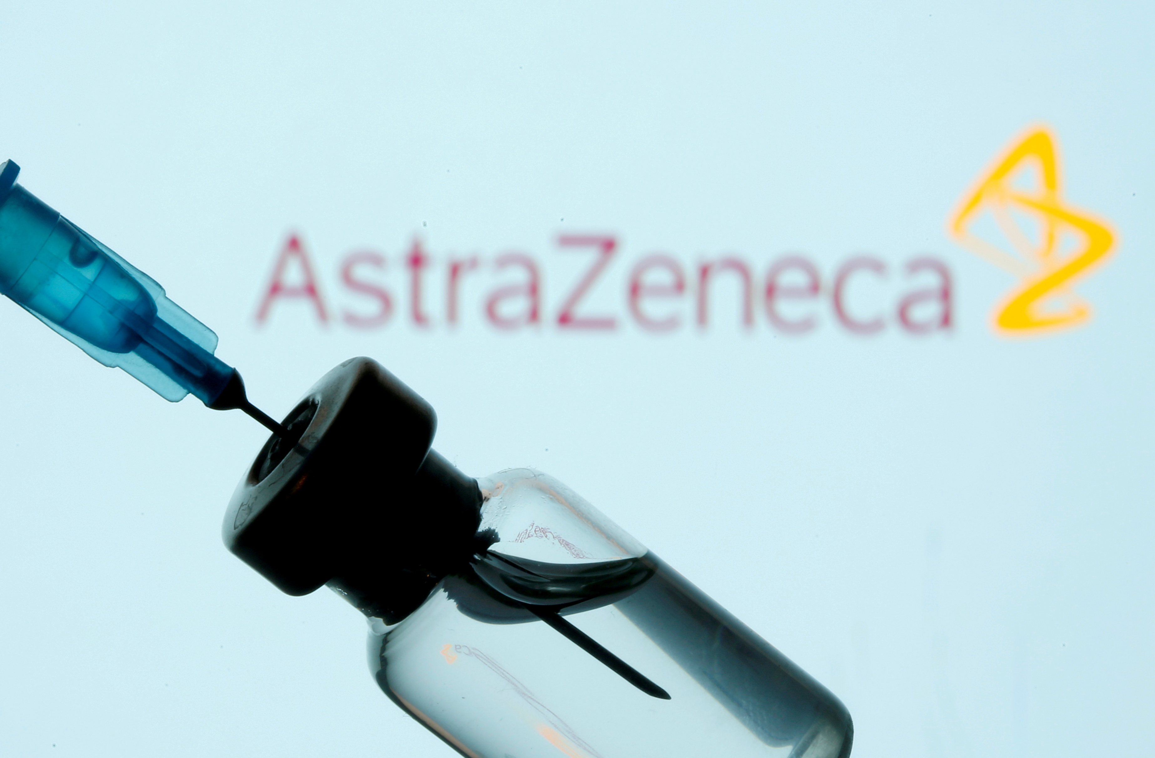 A vial and sryinge are seen in front of a displayed AstraZeneca logo in this illustration taken January 11, 2021. REUTERS/Dado Ruvic/Illustration
