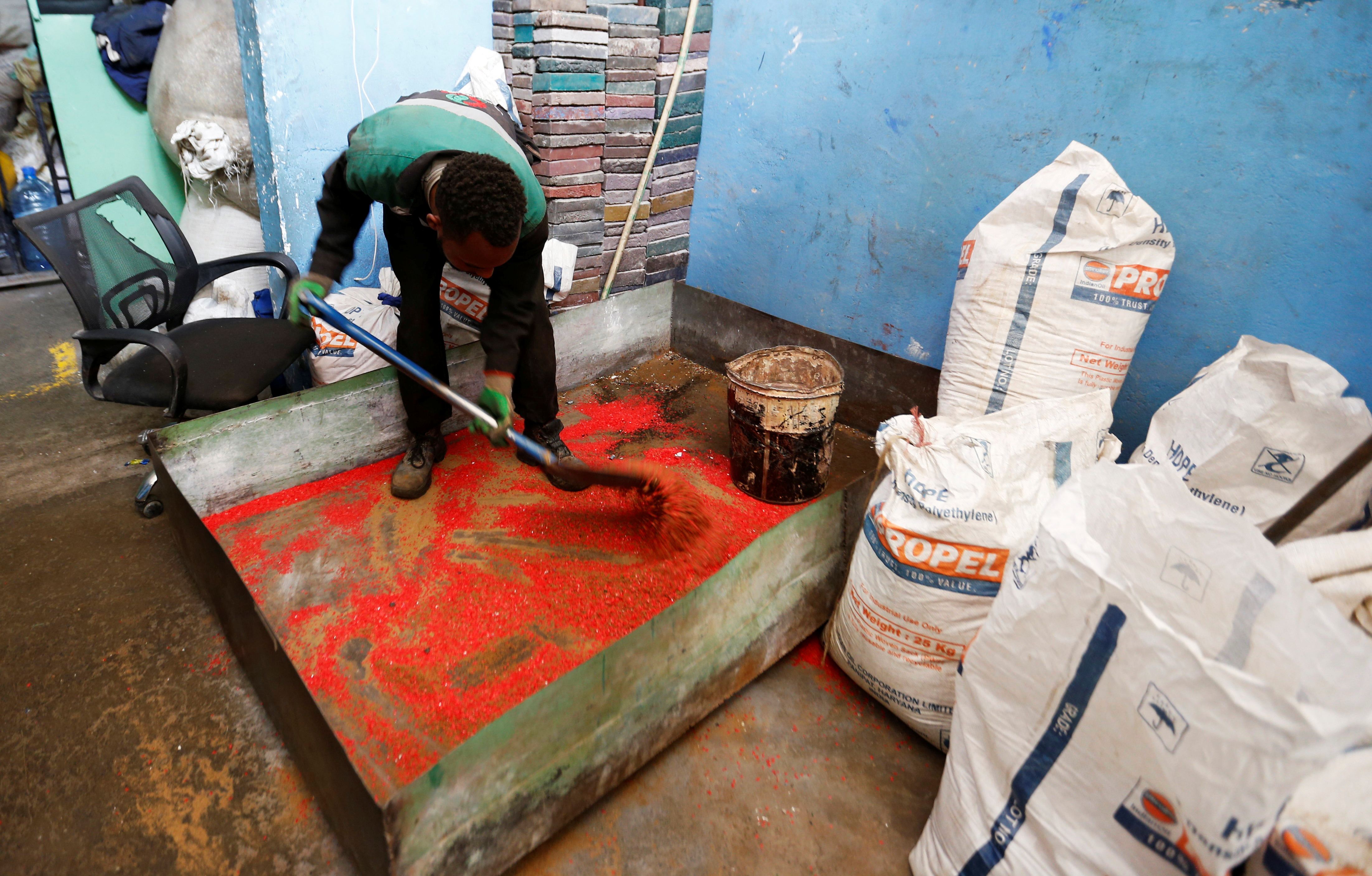 A worker at the Gjenge Makers, a social enterprise that recycles and up-cycles waste plastic into construction products such as paving bricks mixes chips made from recycled plastic in Nairobi, Kenya January 21, 2021. Picture taken January 21, 2021. REUTERS/Thomas Mukoya