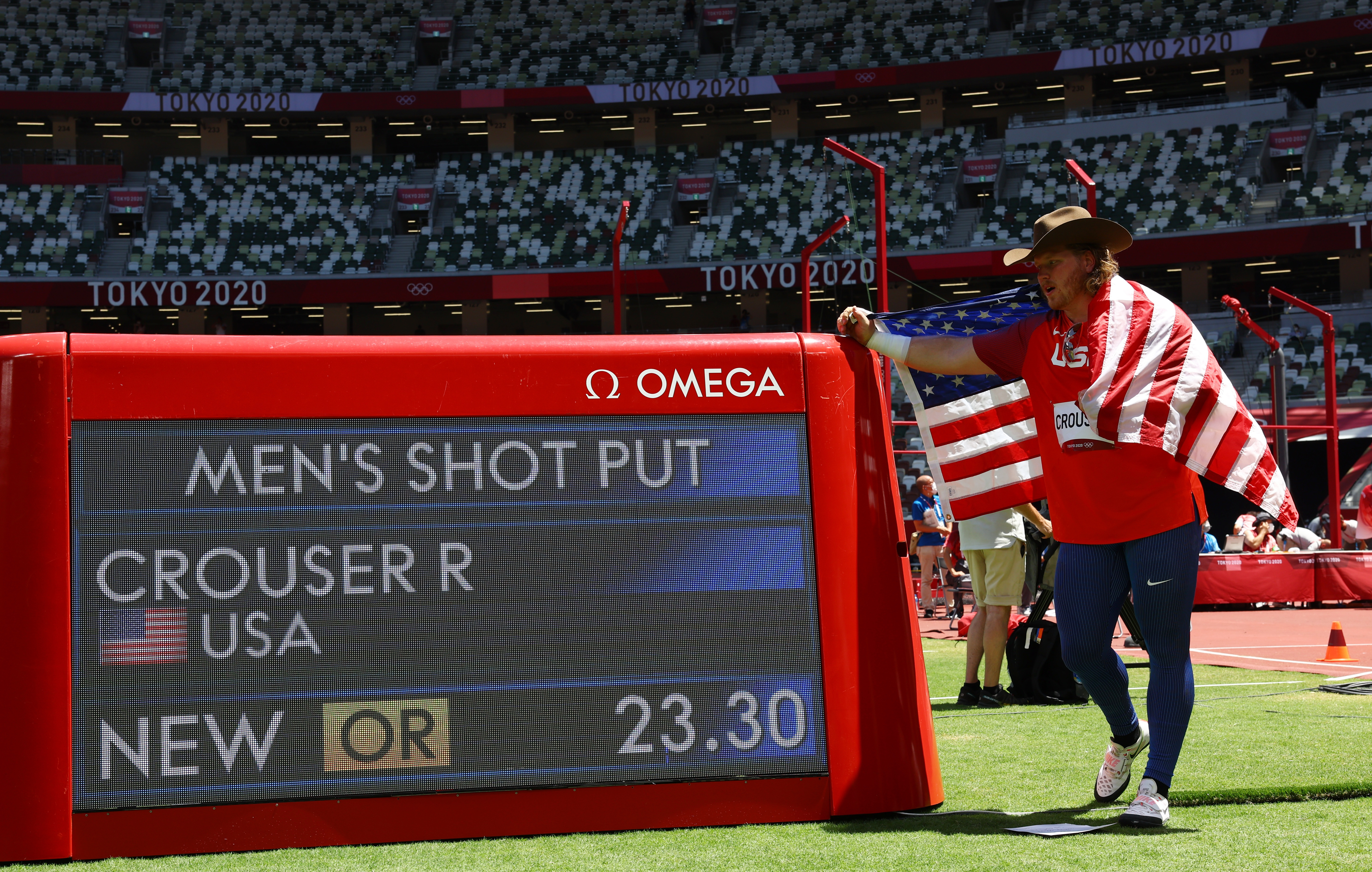 Tokyo 2020 Olympics - Athletics - Men's Shot Put - Final - Olympic Stadium, Tokyo, Japan - August 5, 2021. Ryan Crouser of the United States poses with his national flag after winning gold and a new Olympic Record REUTERS/Kai Pfaffenbach