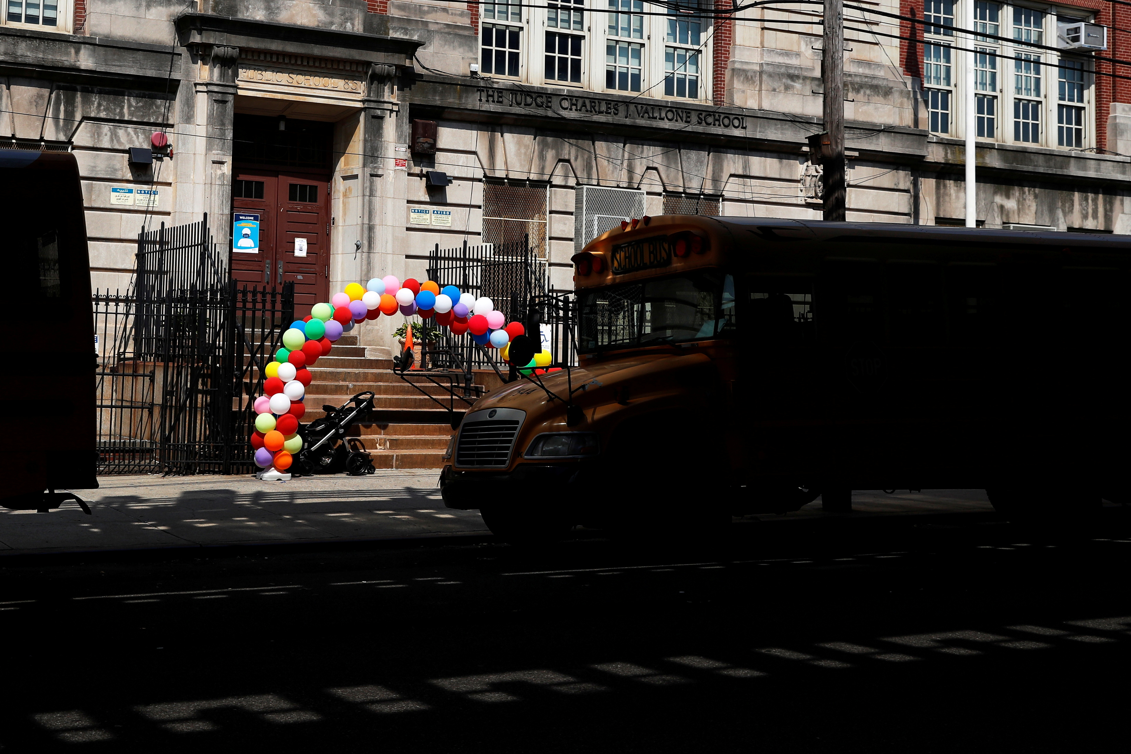 A baby carriage sits at the entrance to elementary Public School 85, amid the coronavirus disease (COVID-19) pandemic, decorated with balloons welcoming students back, in the Queens borough of New York City, U.S., September 13, 2021.  REUTERS/Shannon Stapleton
