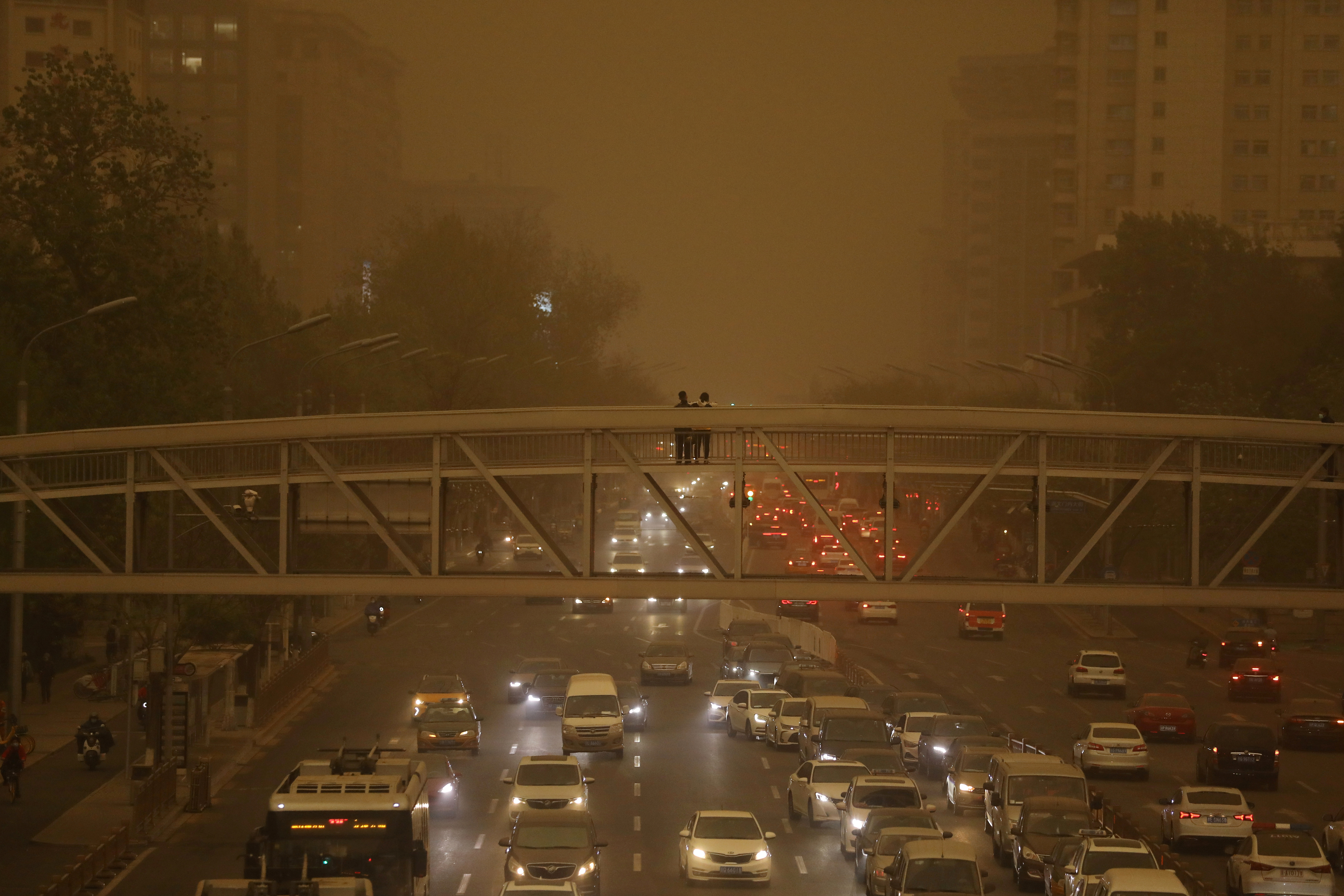 Pedestrians stand on an overpass above car traffic amid a duststorm in Beijing, China April 15, 2021. REUTERS/Tingshu Wang