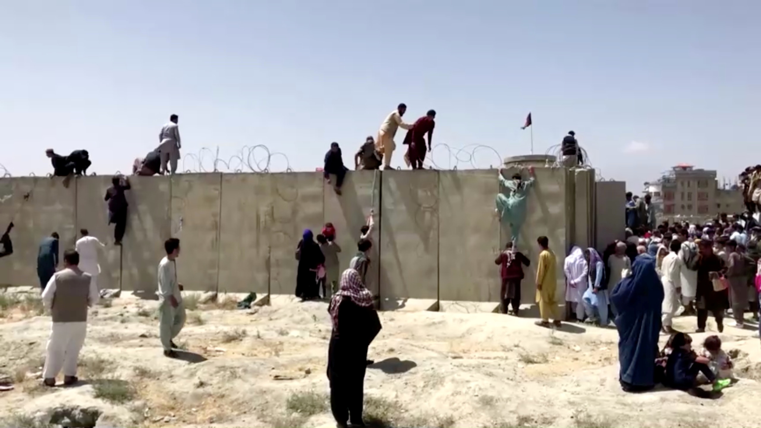 People climb a barbed wire wall to enter the airport in Kabul, Afghanistan August 16, 2021, in this still image taken from a video. REUTERS TV/via REUTERS