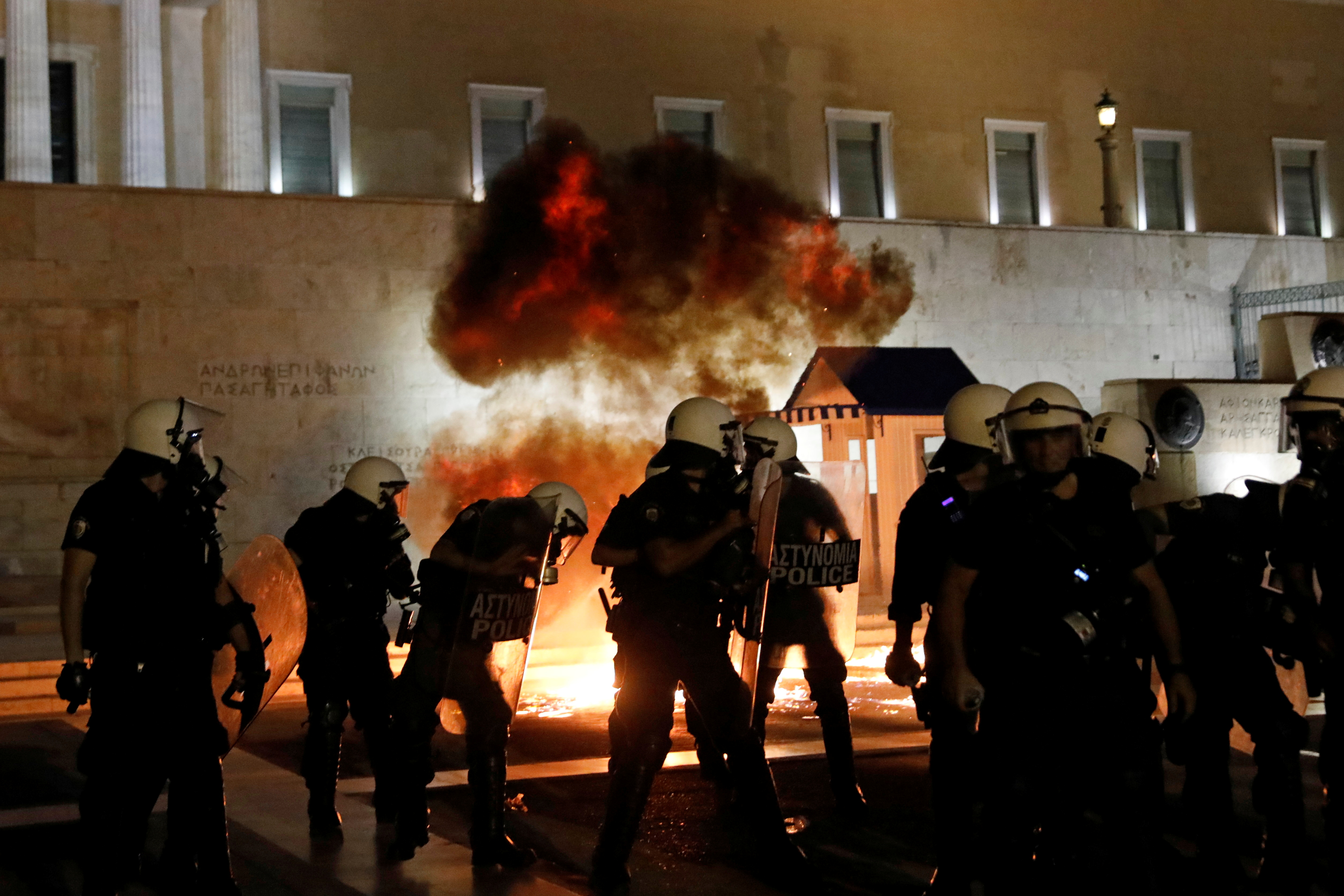 A petrol bomb explodes next to riot police during clashes in a protest against coronavirus disease (COVID-19) vaccinations, in Athens, Greece, July 24, 2021. REUTERS/Costas Baltas
