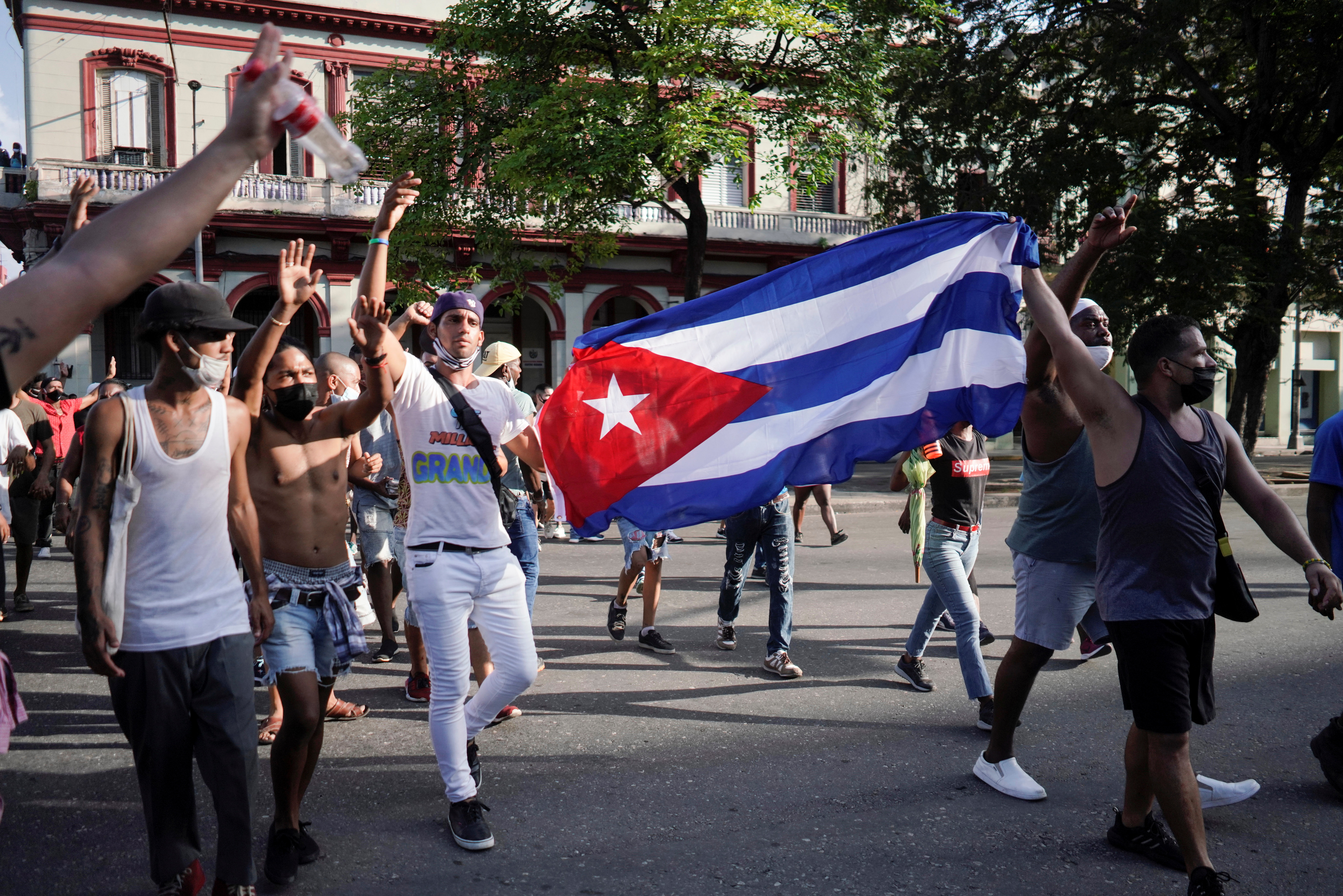 People hold Cuba's national flag during protests against and in support of the government, amidst the coronavirus disease (COVID-19) outbreak, in Havana, Cuba July 11, 2021. REUTERS/Alexandre Meneghini
