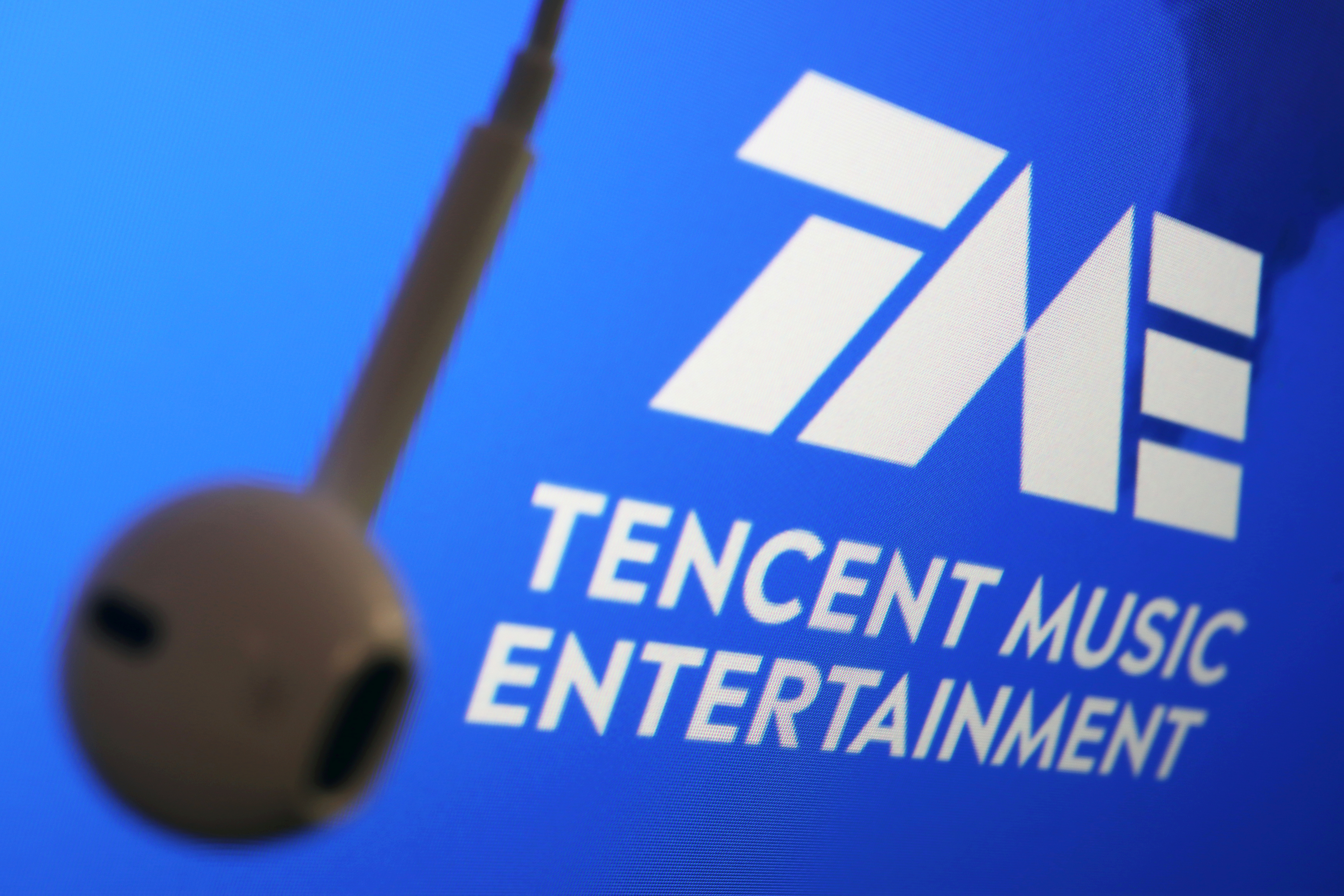 The logo of China's Tencent Music Entertainment Group is seen next to an earphone in this illustration picture taken March 22, 2021. REUTERS/Florence Lo/Illustration