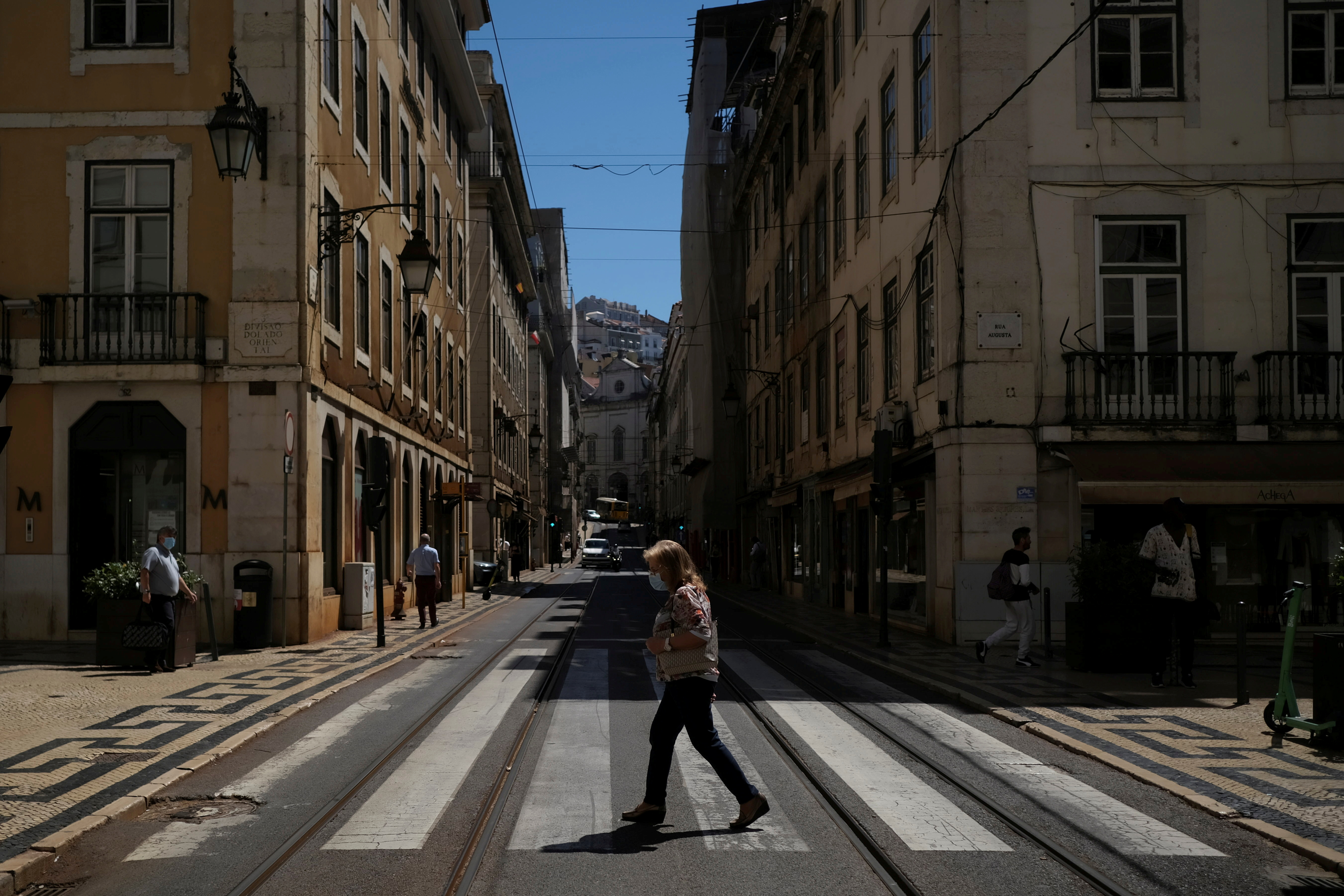 A person wearing a protective mask walks in Lisbon downtown amid the coronavirus disease (COVID-19) pandemic, in Lisbon, Portugal, June 24, 2021. REUTERS/Pedro Nunes/File Photo