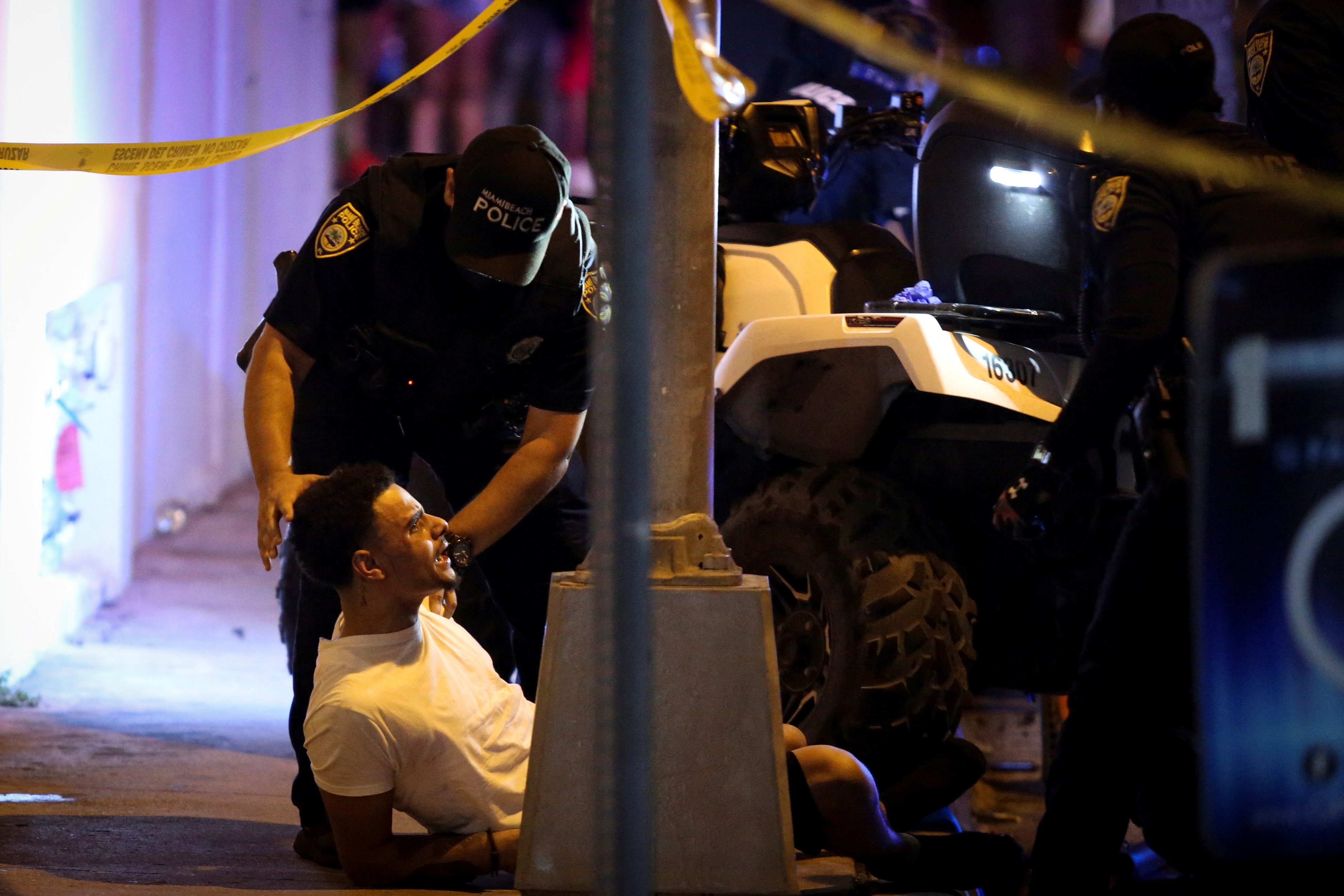 Police officers detain a man as they enforce an 8pm curfew imposed by local authorities on spring break festivities, amid the coronavirus disease (COVID-19) pandemic, in Miami Beach, Florida, U.S., March 20, 2021. REUTERS/Marco Bello    DAY