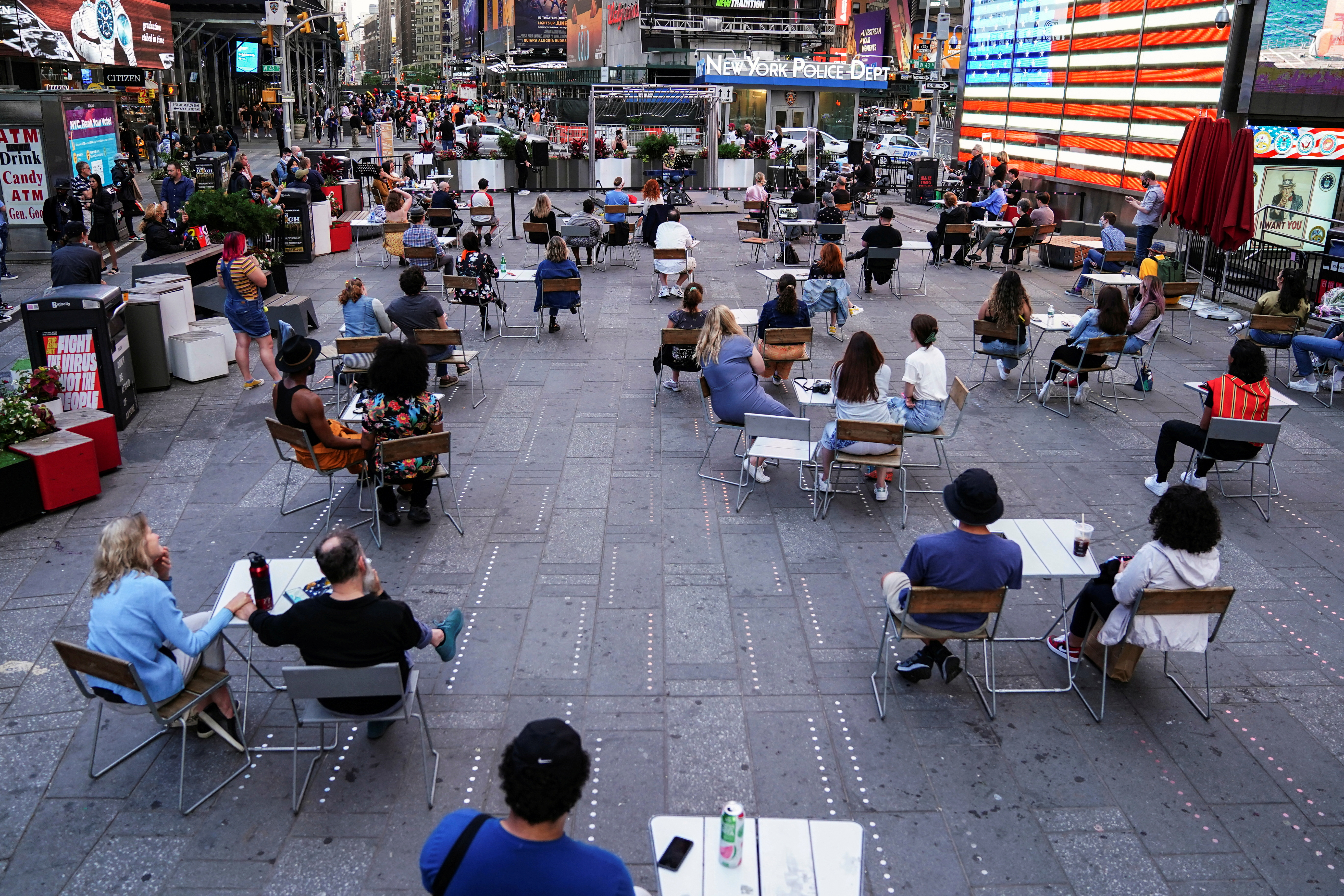 People sit socially distanced while watching a concert in Times Square in the Manhattan borough of New York City, New York, U.S., June 1, 2021.  REUTERS/Carlo Allegri/File Photo