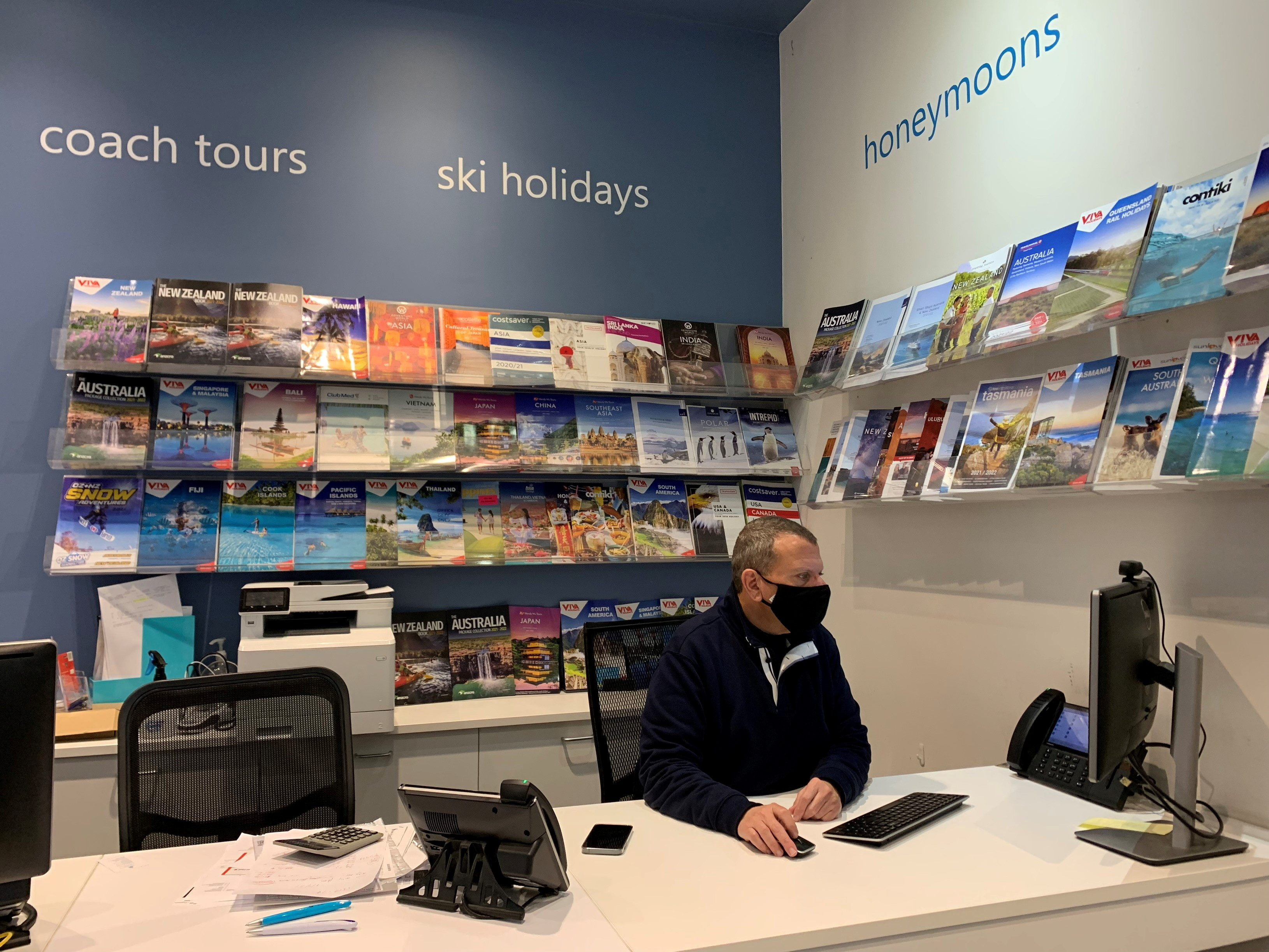 Travel consultant Phillip Koinis sits behind the desk at Oxford Travel agency as Australia's conservative approach to reopening and slow rollout of coronavirus disease (COVID-19) vaccinations has adversely affected the tourism industry, in Sydney, Australia, July 5, 2021.  REUTERS/Stefica Nicol Bikes