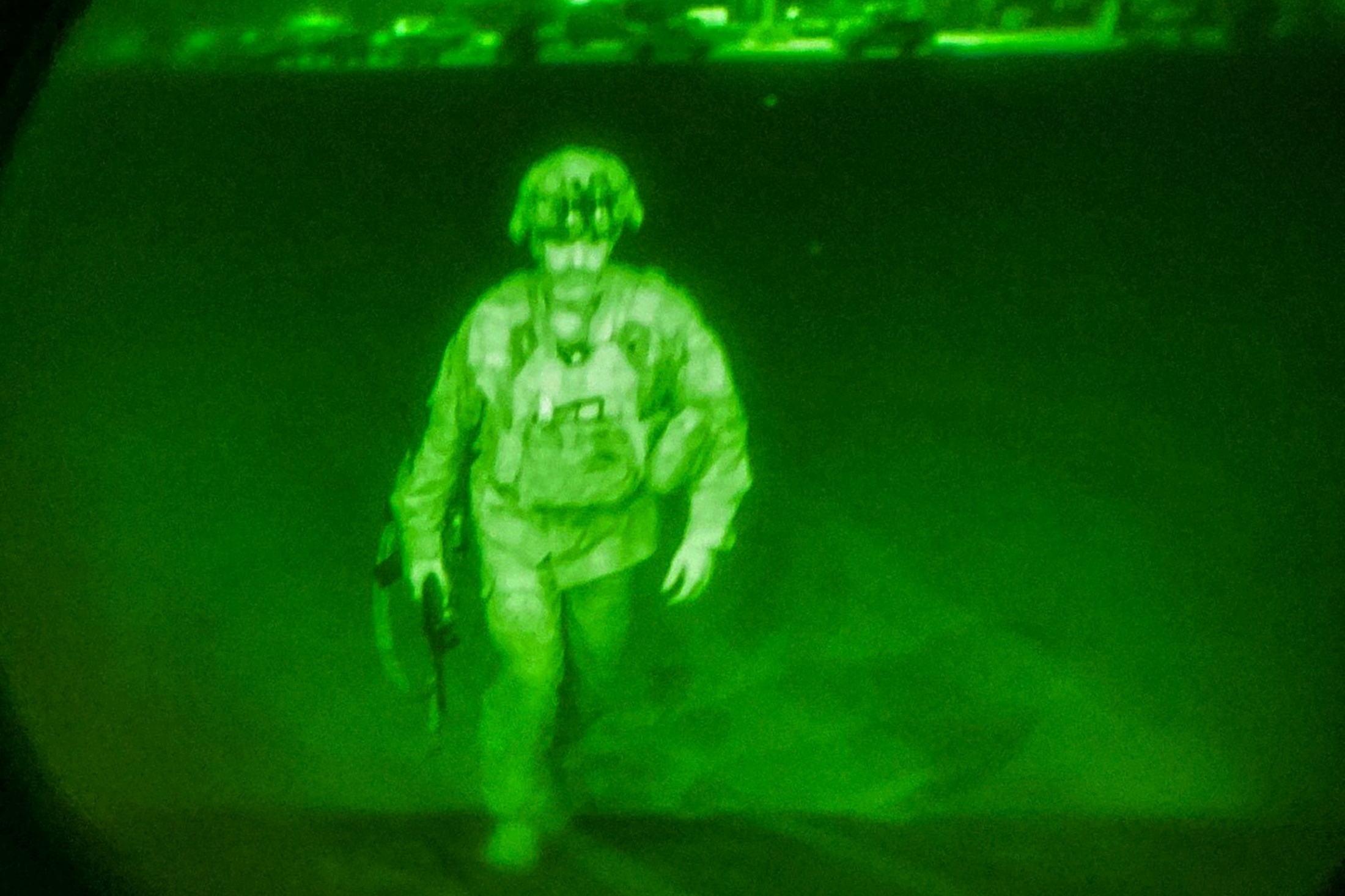 U.S. Army Major General Chris Donahue, commander of the 82nd Airborne Division, steps on board a C-17 transport plane as the last U.S. service member to leave Hamid Karzai International Airport in Kabul, Afghanistan August 30, 2021 in a photograph taken using night vision optics.  XVIII Airborne Corps/Handout via REUTERS