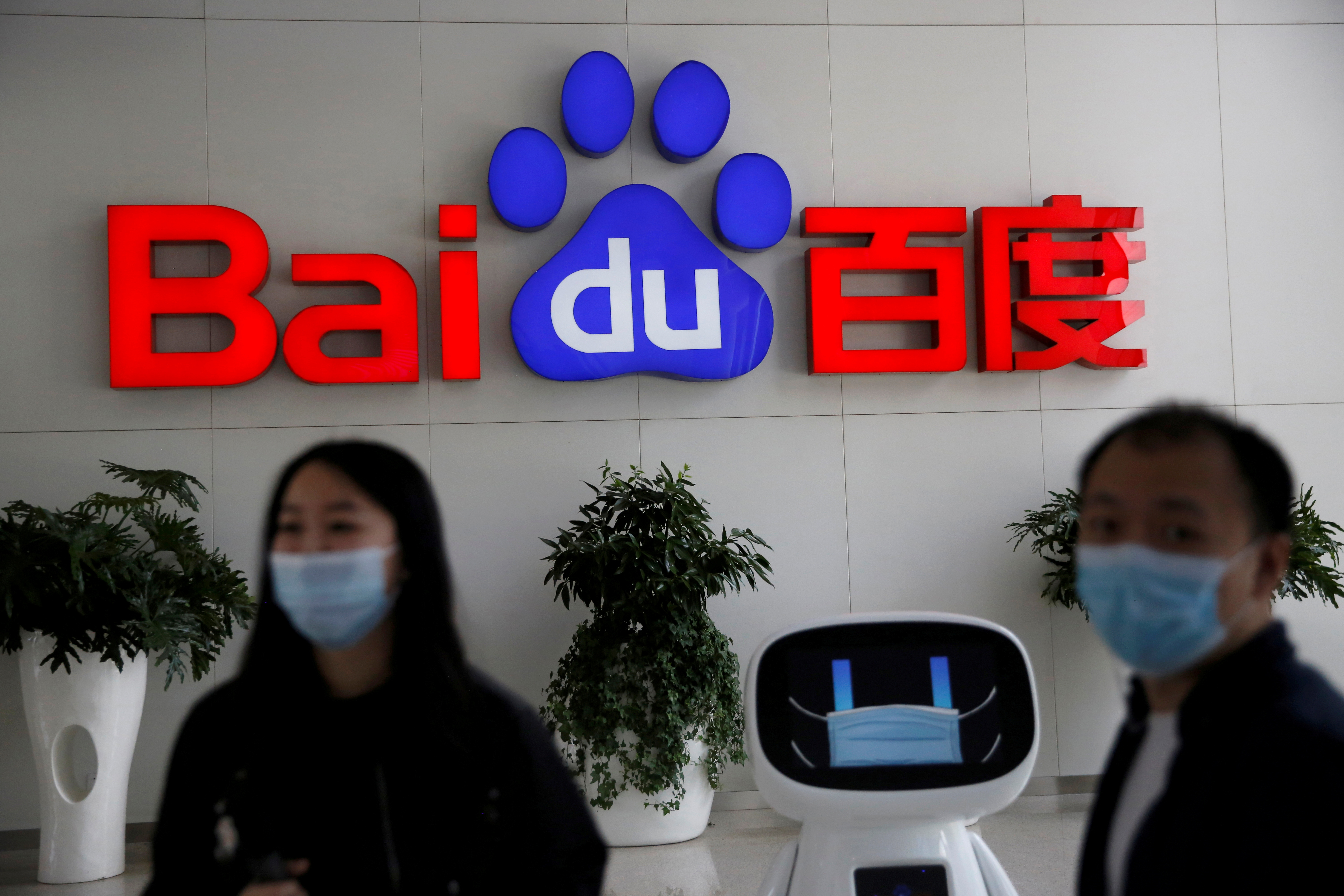 Employees wearing face masks are seen next to a Baidu AI robot, in front of a sign of Baidu at the company's headquarters in Beijing, following the novel coronavirus disease (COVID-19) outbreak, China May 18, 2020. REUTERS/Tingshu Wang