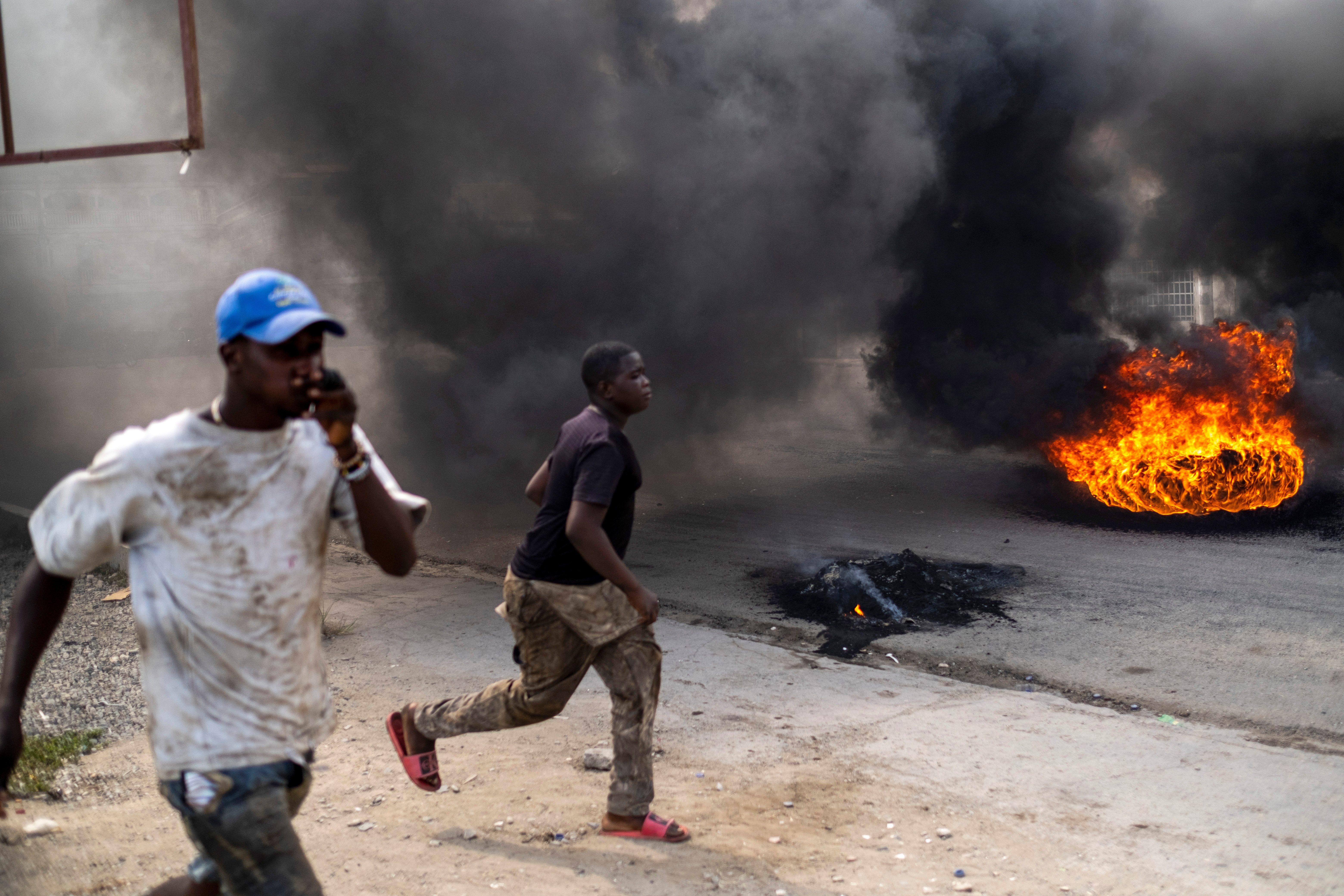 People walk along a street filled with smoke from burning tires during a protest against the assassination of Haitian President Jovenel Moise in Cap-Haitien, Haiti July 22, 2021. REUTERS/Ricardo Arduengo