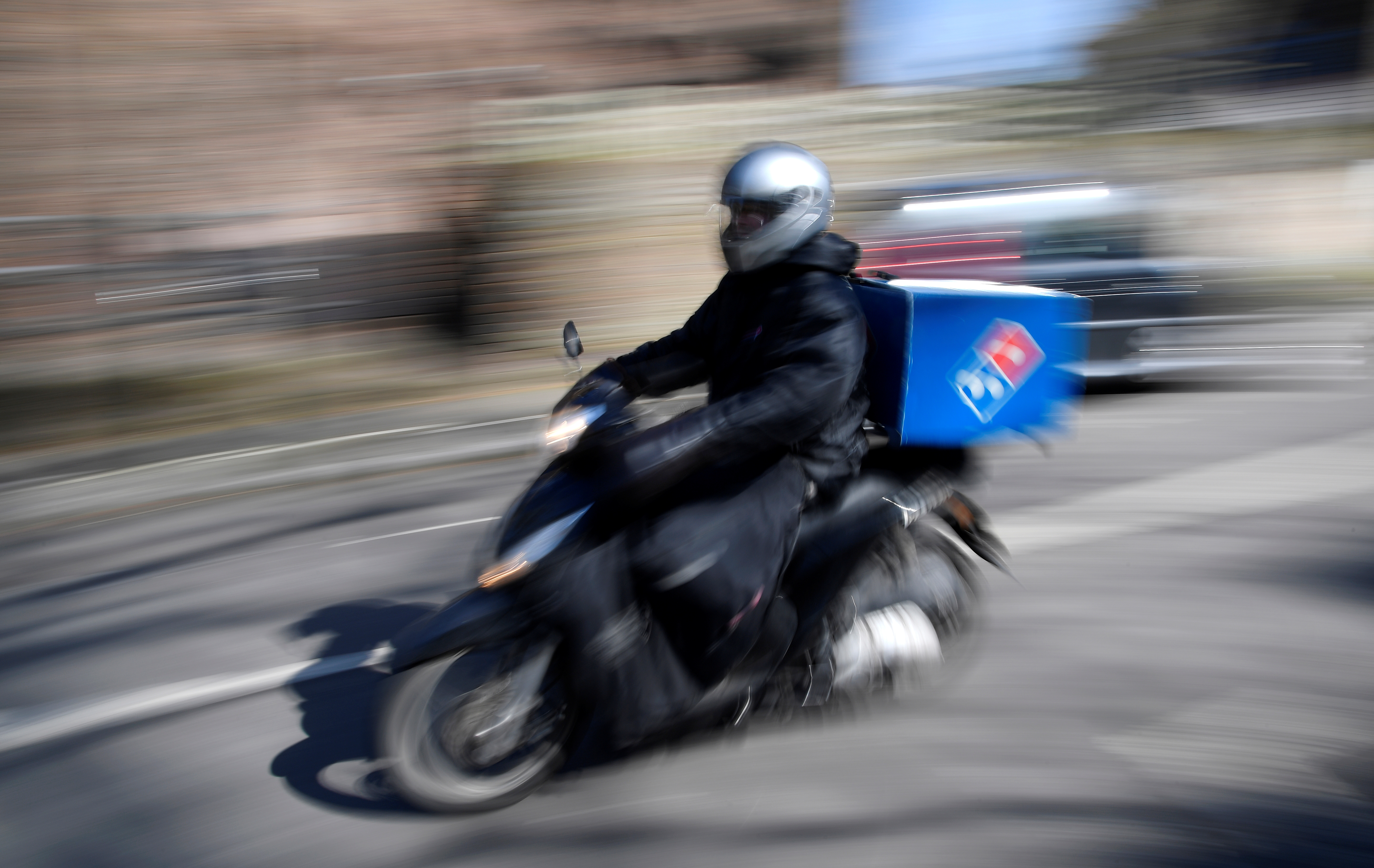 A Dominoes pizza delivery driver rides a motorbike in a residential street in West London as the spread of the coronavirus disease (COVID-19) continues, in London, Britain, March 24, 2020. REUTERS/Toby Melville/File photo