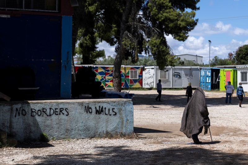 A woman walks past graffiti inside the Ritsona camp for refugees and migrants, in Greece, June 15, 2021. REUTERS/Alkis Konstantinidis