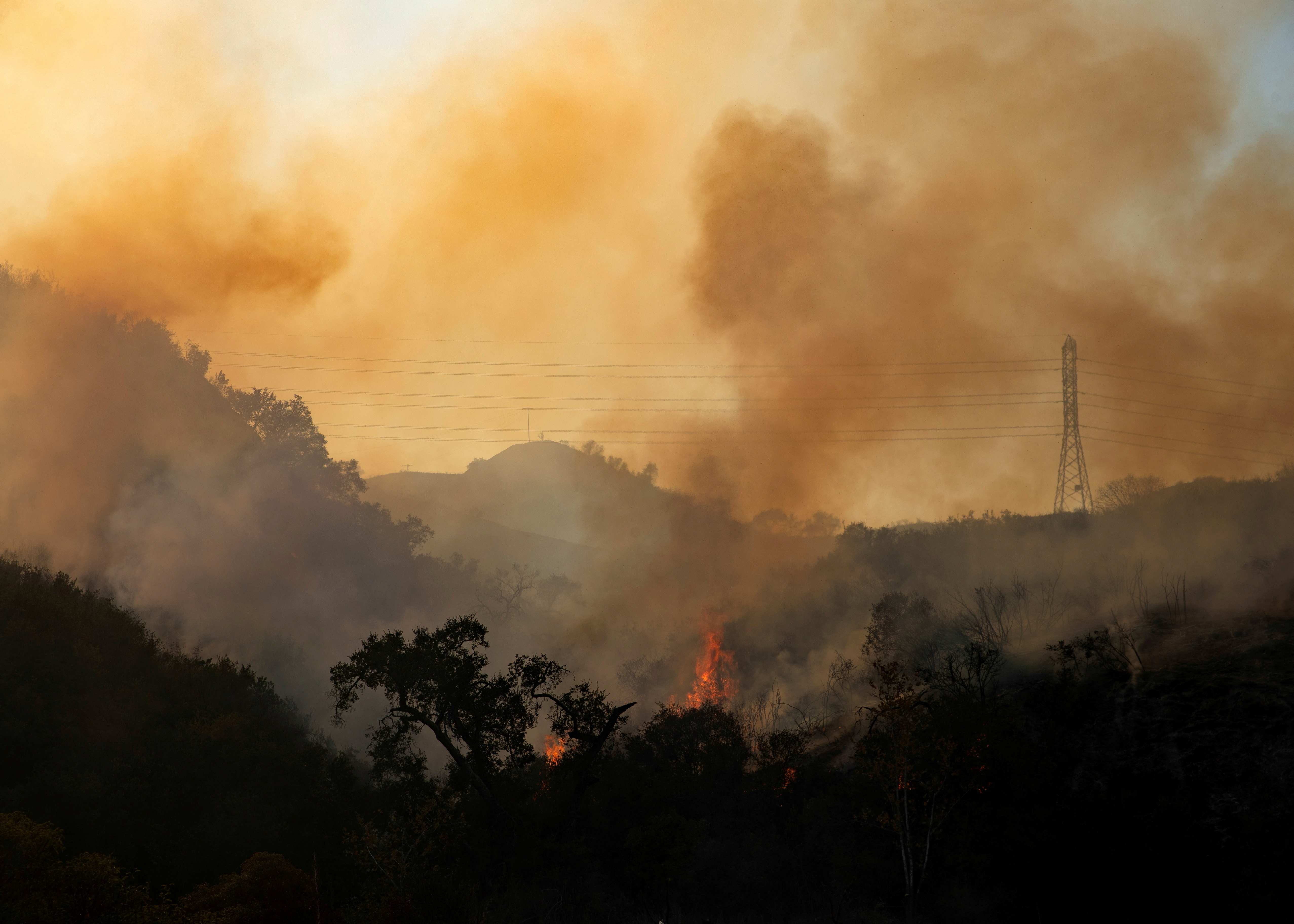 The Bond Fire wildfire continues to burn next to electrical power lines near Modjeska Canyon, California, U.S., December 3, 2020.  REUTERS/Mike Blake/File Photo