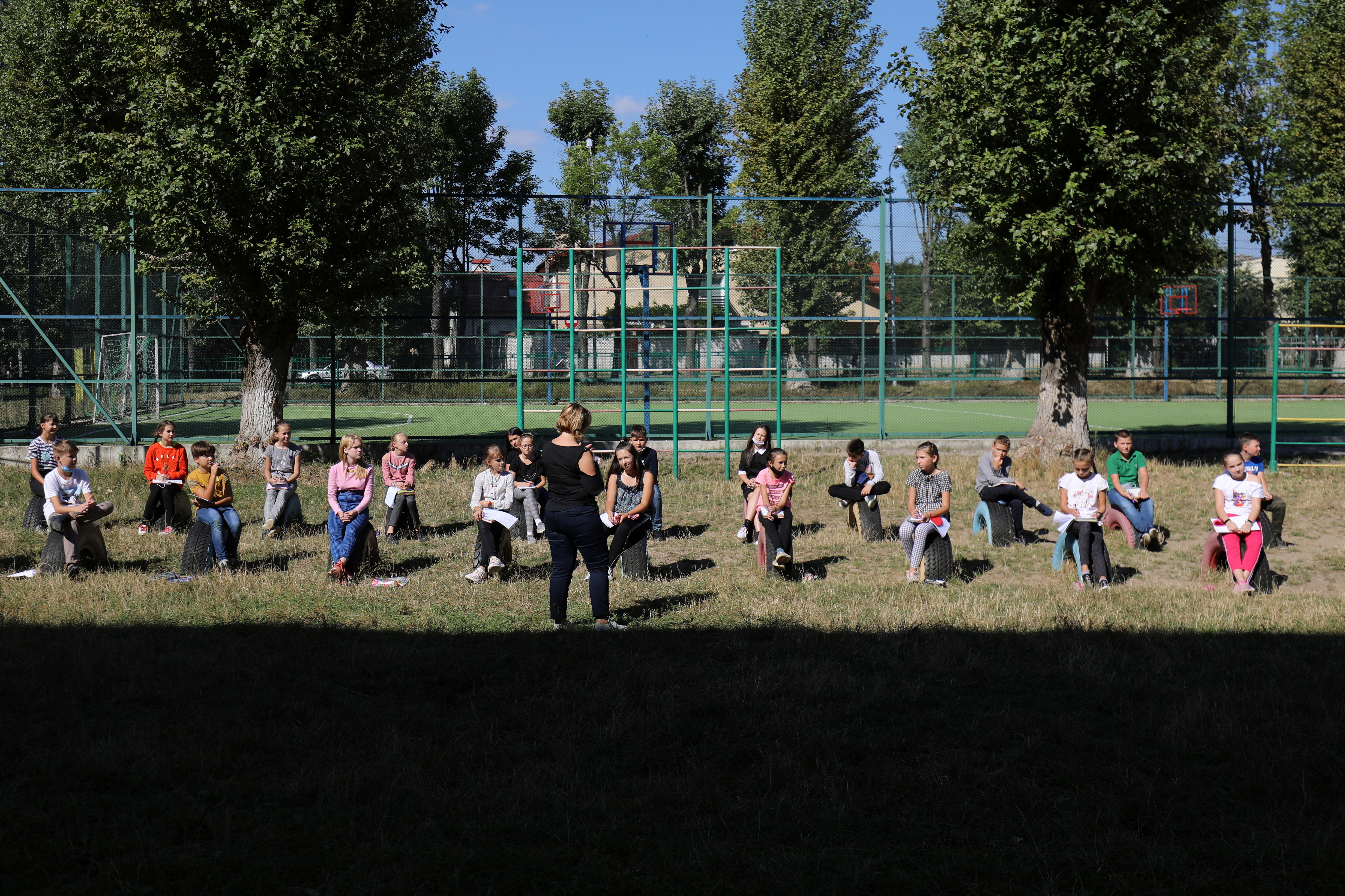 Students attend a geography class at a school in an open-air classroom organised on a playground amid the coronavirus disease (COVID-19) outbreak, in Lviv, Ukraine September 9, 2020.  REUTERS/Roman Baluk