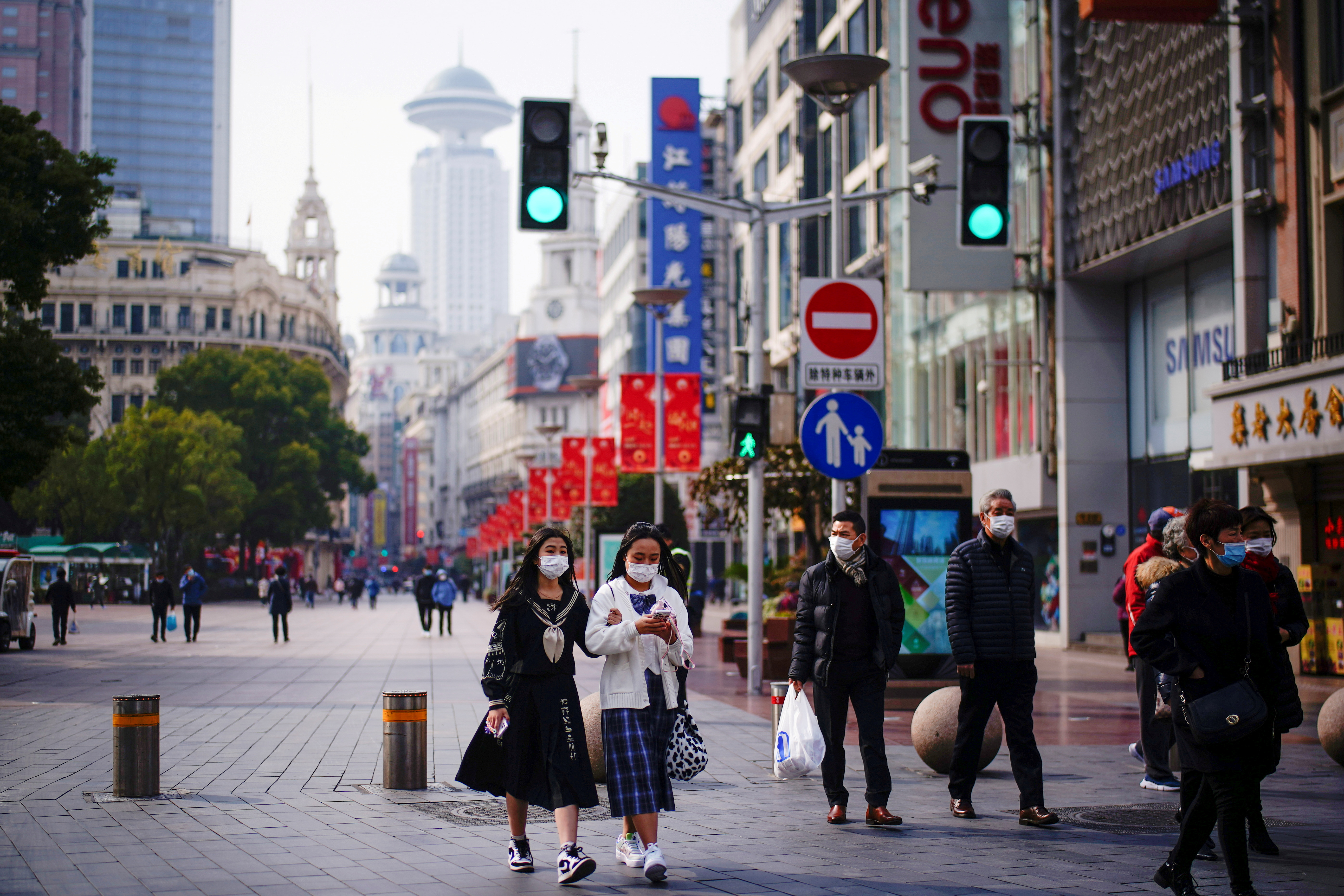 People wearing face masks walk at a main shopping area, following the coronavirus disease (COVID-19) outbreak in Shanghai, China January 27, 2021. REUTERS/Aly Song