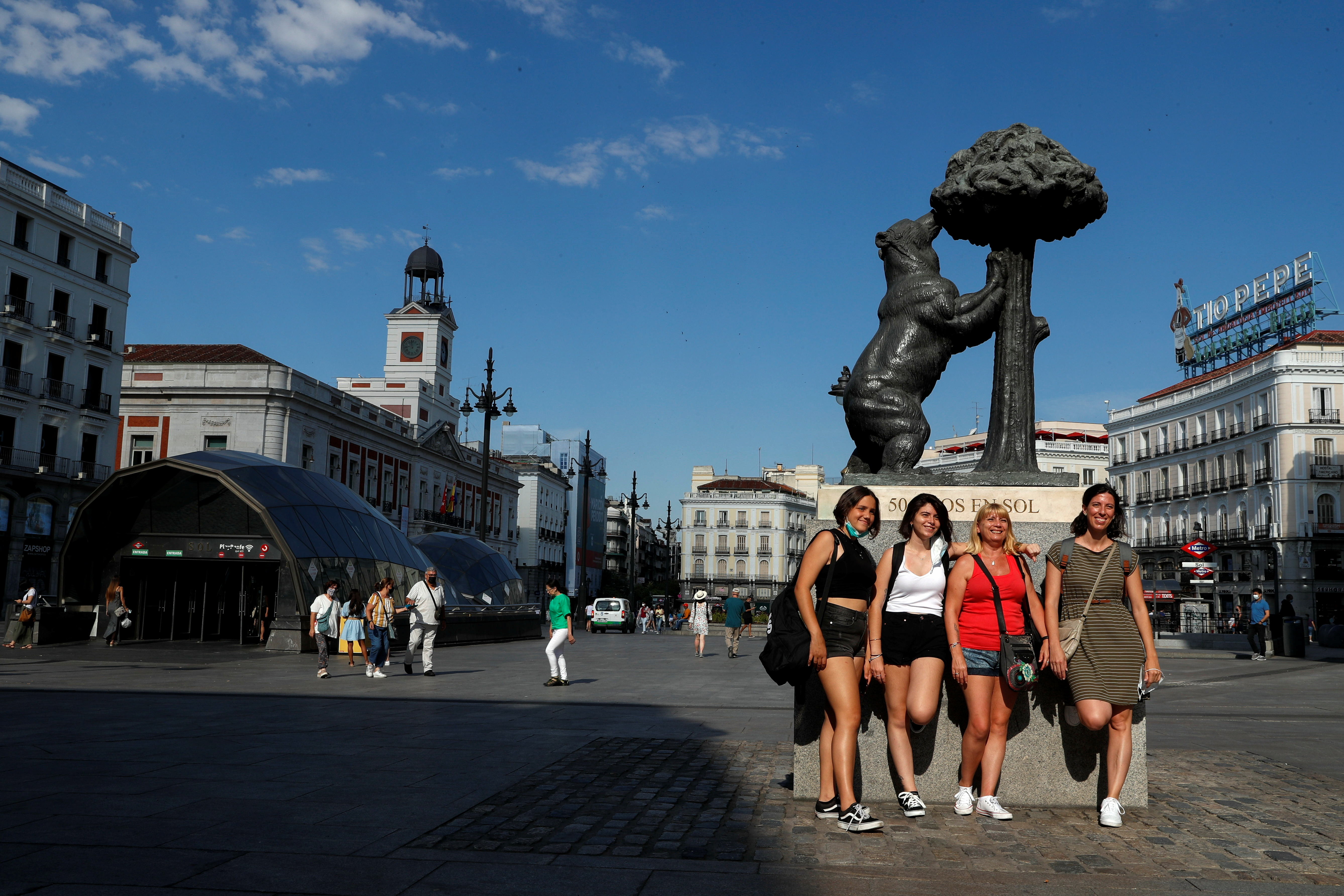 Women pose at Puerta del Sol square without their masks on as they are no longer required outdoors from June 26, amid the coronavirus disease (COVID-19) pandemic in Madrid, Spain, June 26, 2021. REUTERS/Susana Vera