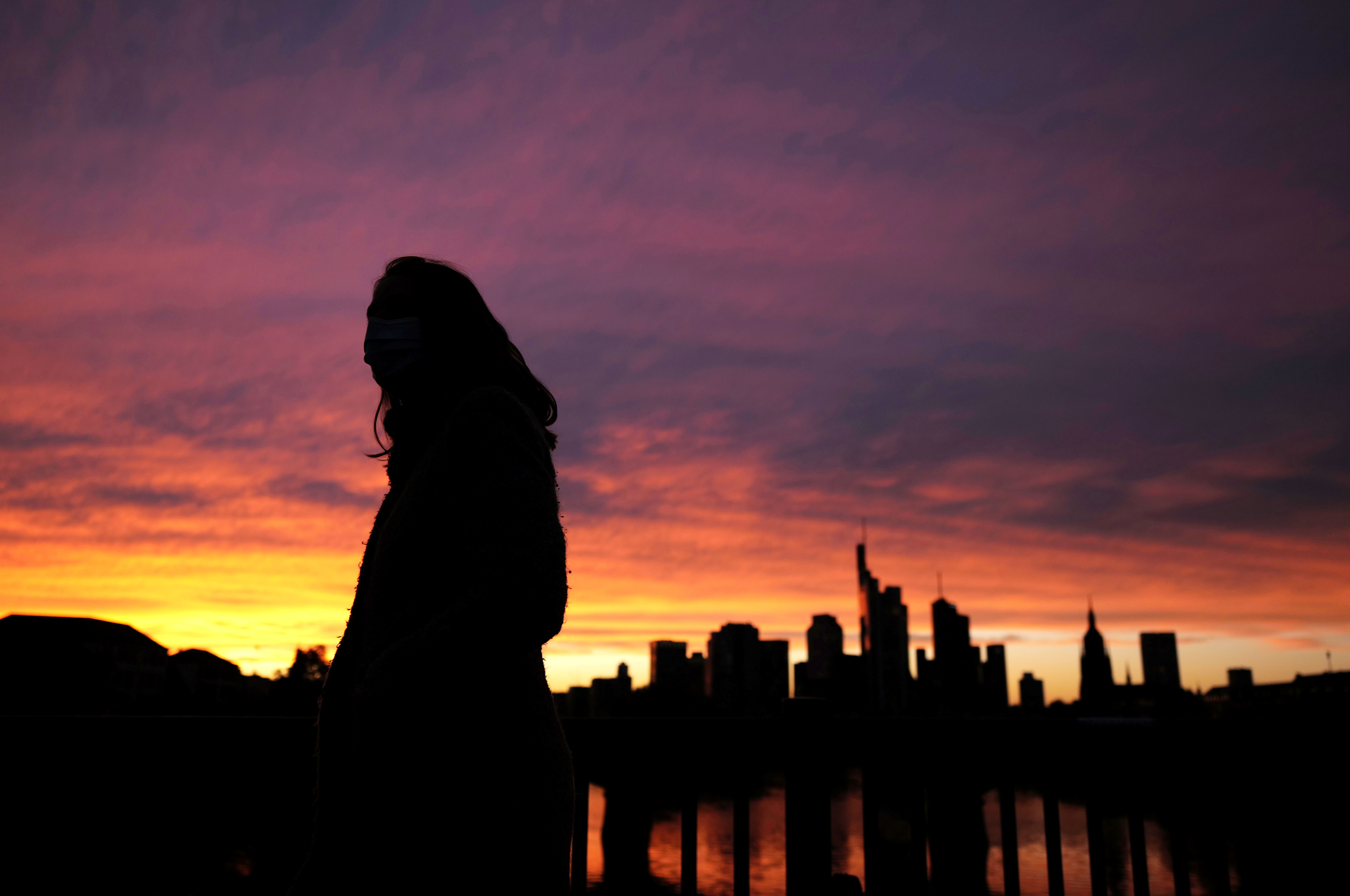 A woman wearing a protective mask walks past the skyline of the financial district during sunset as the spread of the coronavirus disease (COVID-19) continues in Frankfurt, Germany, October 26, 2020, REUTERS/Kai Pfaffenbach