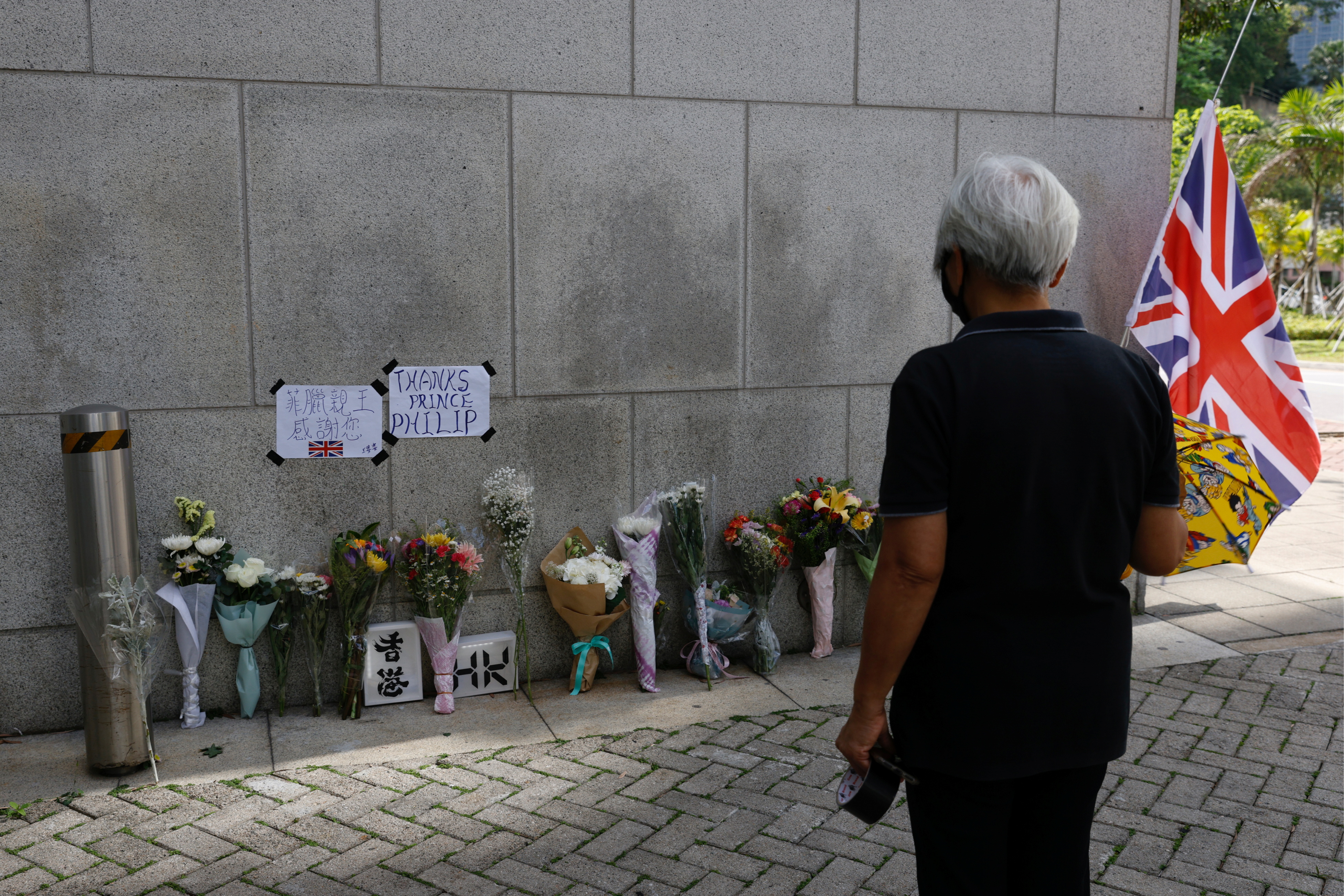 Flowers lie outside the British Consulate-General, Hong Kong, after Britain's Prince Philip, husband of Queen Elizabeth, died at the age of 99, in China April 10, 2021. REUTERS/Tyrone Siu