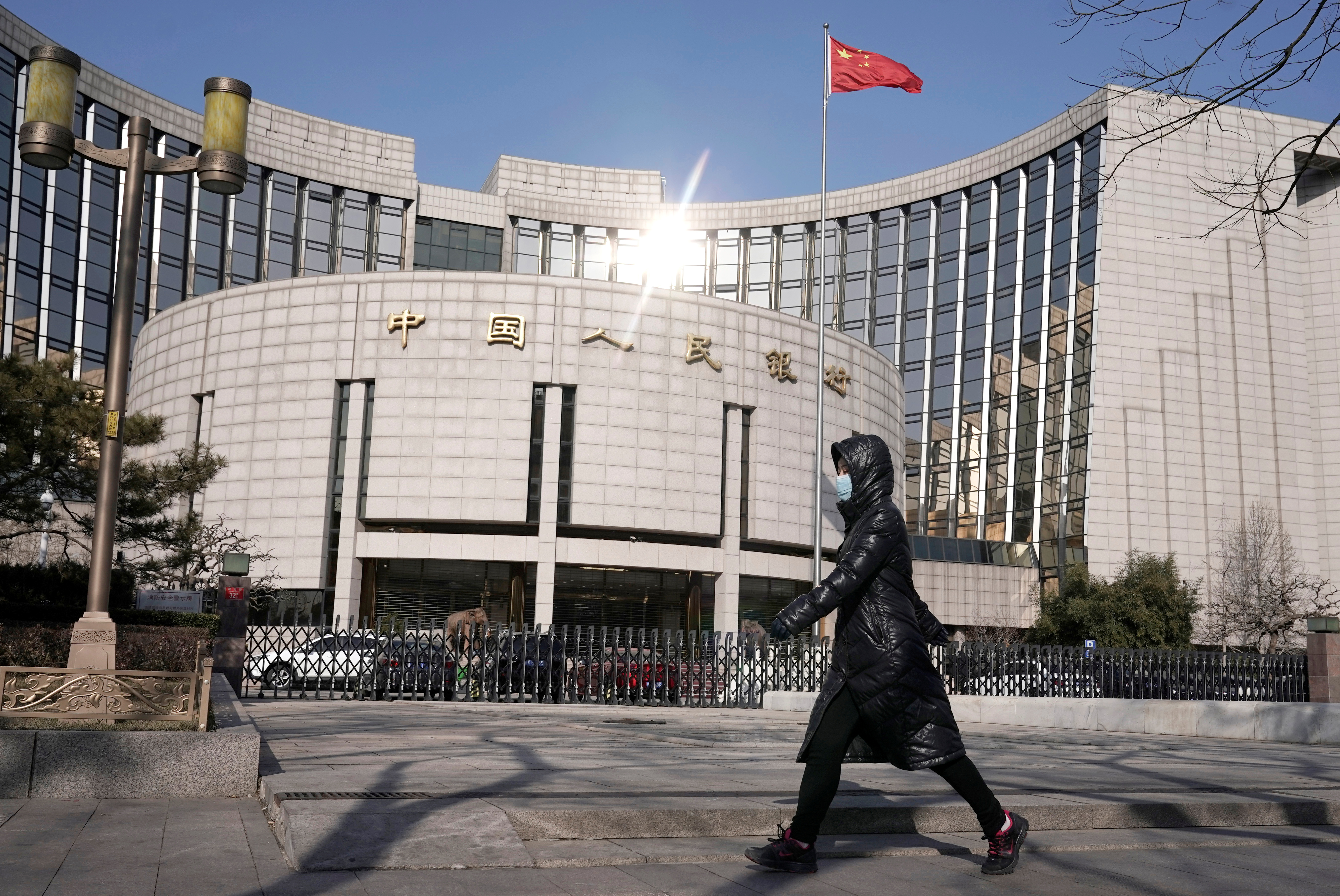A woman wearing a mask walks past the headquarters of the People's Bank of China, the central bank, in Beijing, China, as the country is hit by an outbreak of the new coronavirus, February 3, 2020. REUTERS/Jason Lee