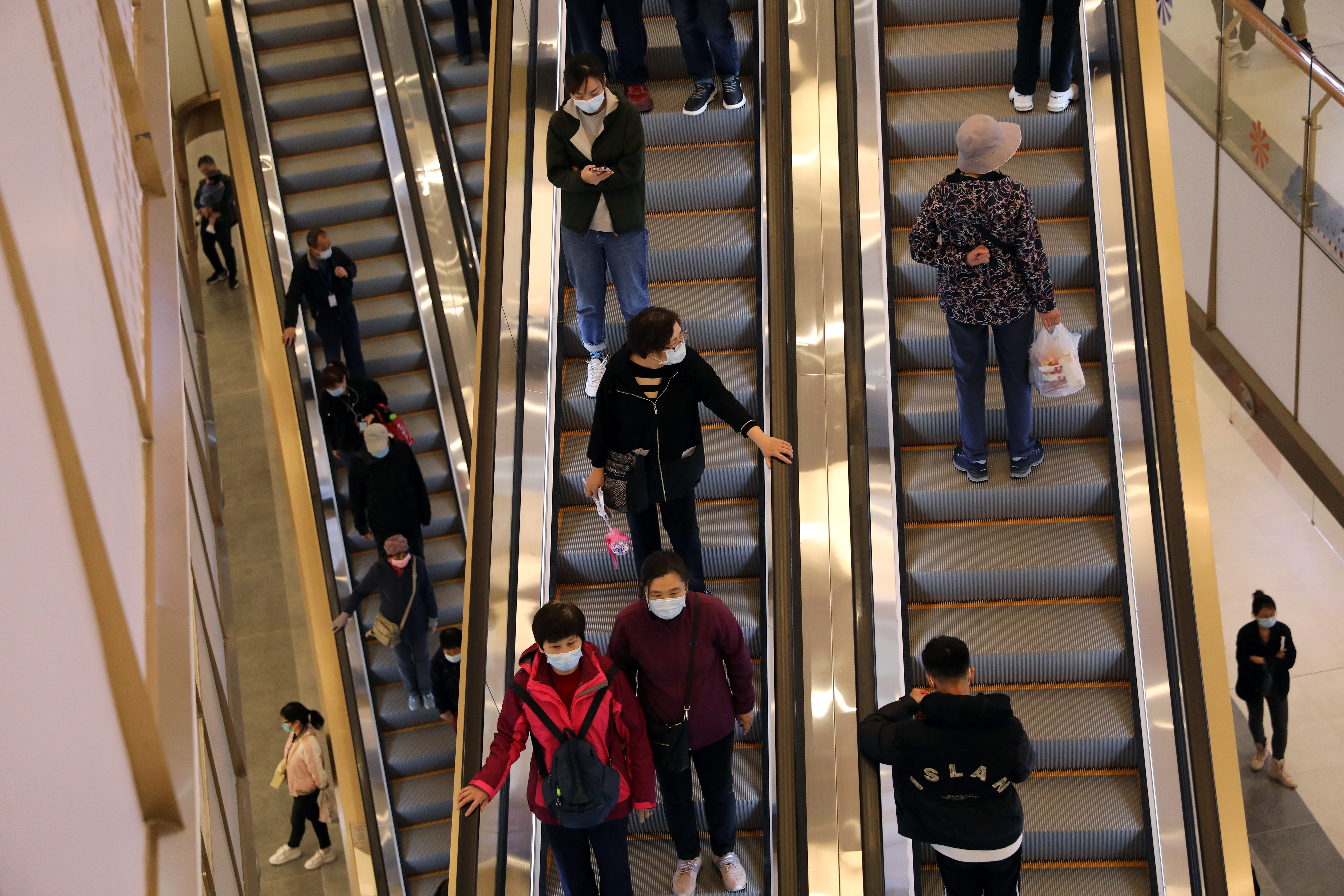 People ride elevators at a newly opened shopping mall in Beijing, China April 16, 2021. REUTERS/Tingshu Wang