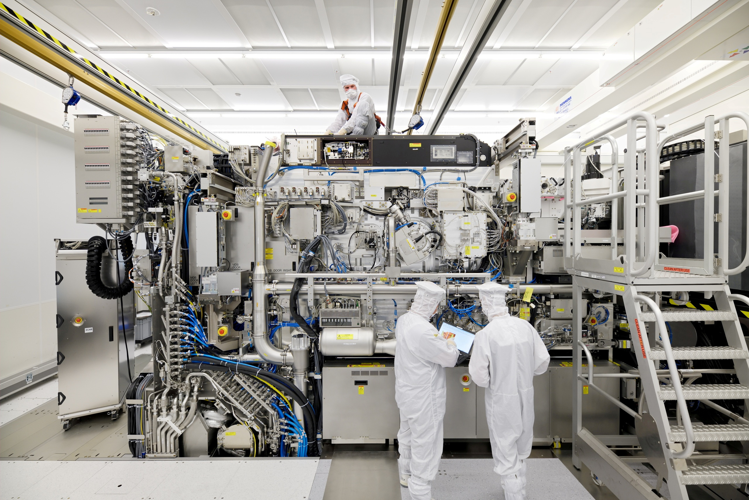 Employees are seen working on the final assembly of ASML's TWINSCAN NXE:3400B semiconductor lithography tool with its panels removed, in Veldhoven, Netherlands, in this picture taken April 4, 2019. Bart van Overbeeke Fotografie/ASML/Handout via REUTERS /File Photo