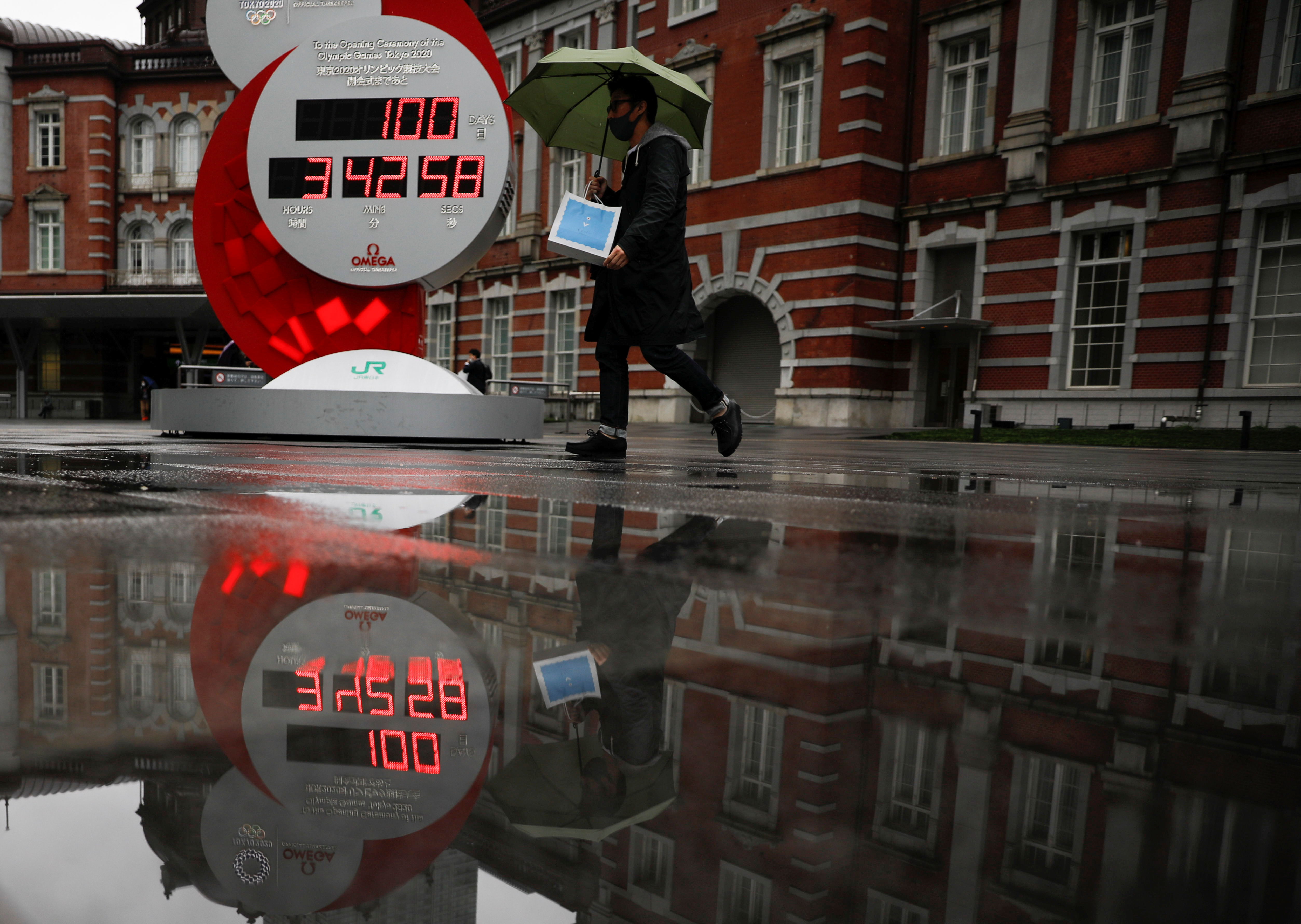 A countdown clock showing that 100 days are left until Tokyo 2020 Olympic Games that have been postponed to 2021 due to the coronavirus disease (COVID-19) pandemic is reflected in a puddle in Tokyo, Japan April 14, 2021.   REUTERS/Issei Kato