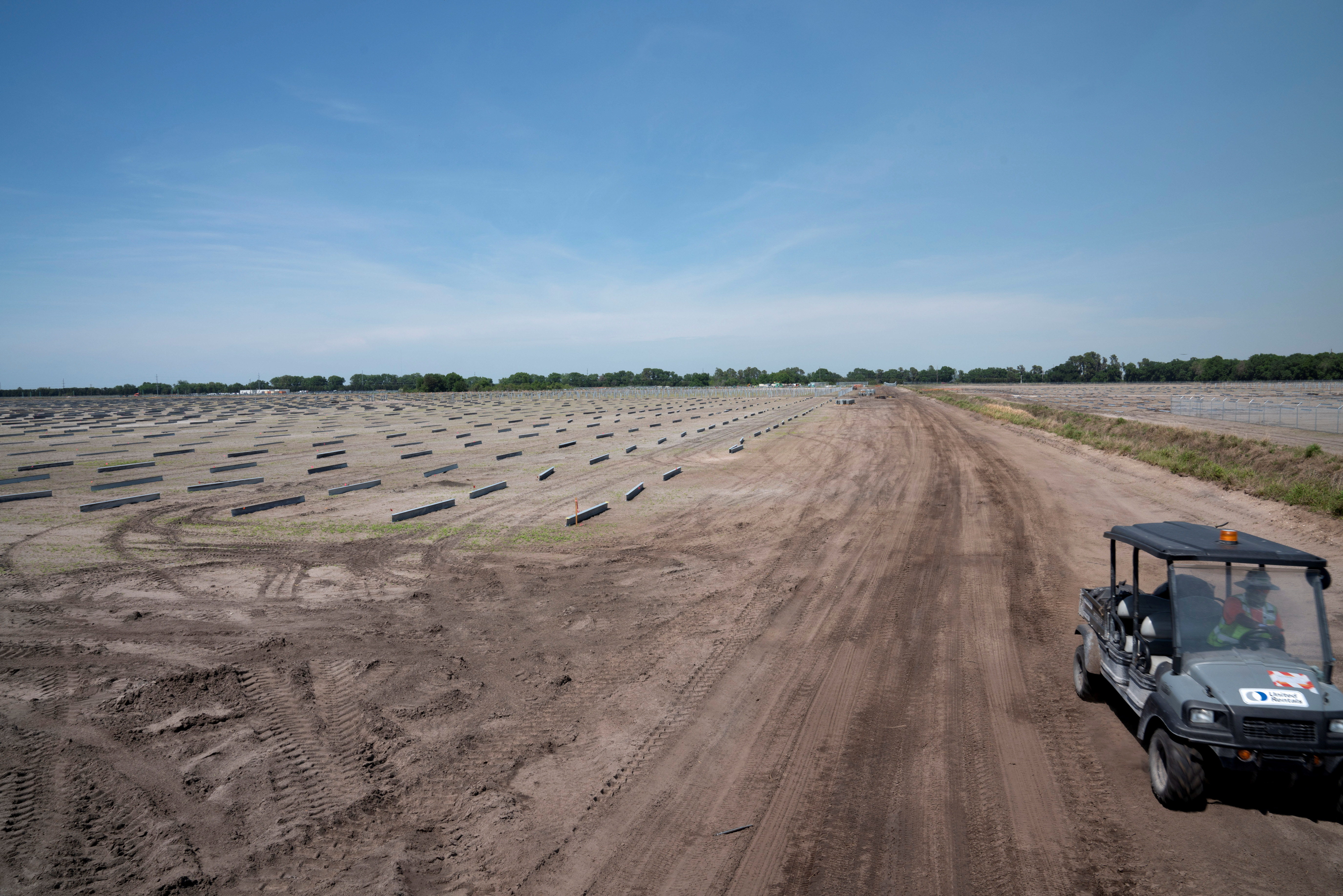 A construction worker drives past a field of metal piles at the Duette solar site being developed on previously agricultural land in Bowling Green, Florida, U.S., March 24, 2021. REUTERS/Dane Rhys