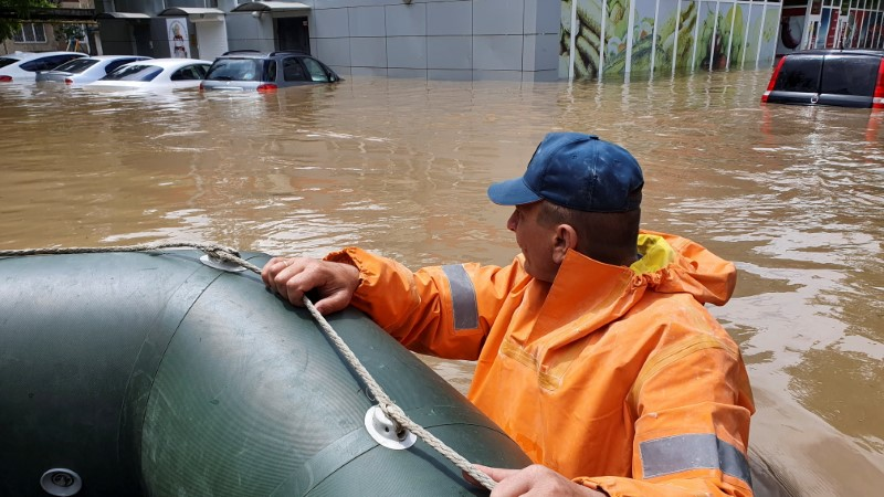 A rescuer pulls a boat in a flooded street following heavy rainfall in Kerch, Crimea June 17, 2021. REUTERS/Alla Dmitrieva