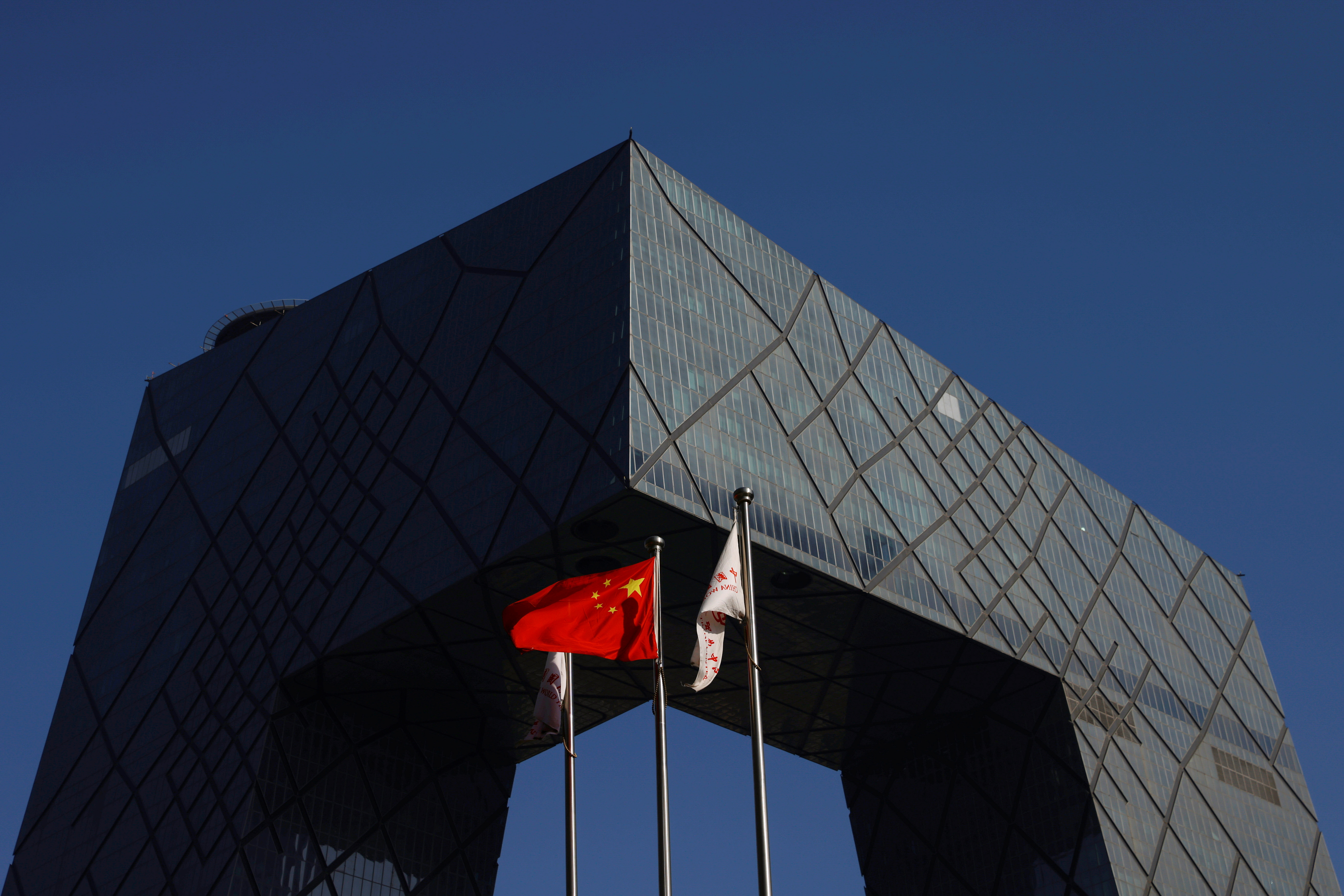 A Chinese flag flutters outside the CCTV headquarters, the home of Chinese state media outlet CCTV and its English-language sister channel CGTN, in Beijing, China February 5, 2021. REUTERS/Carlos Garcia Rawlins