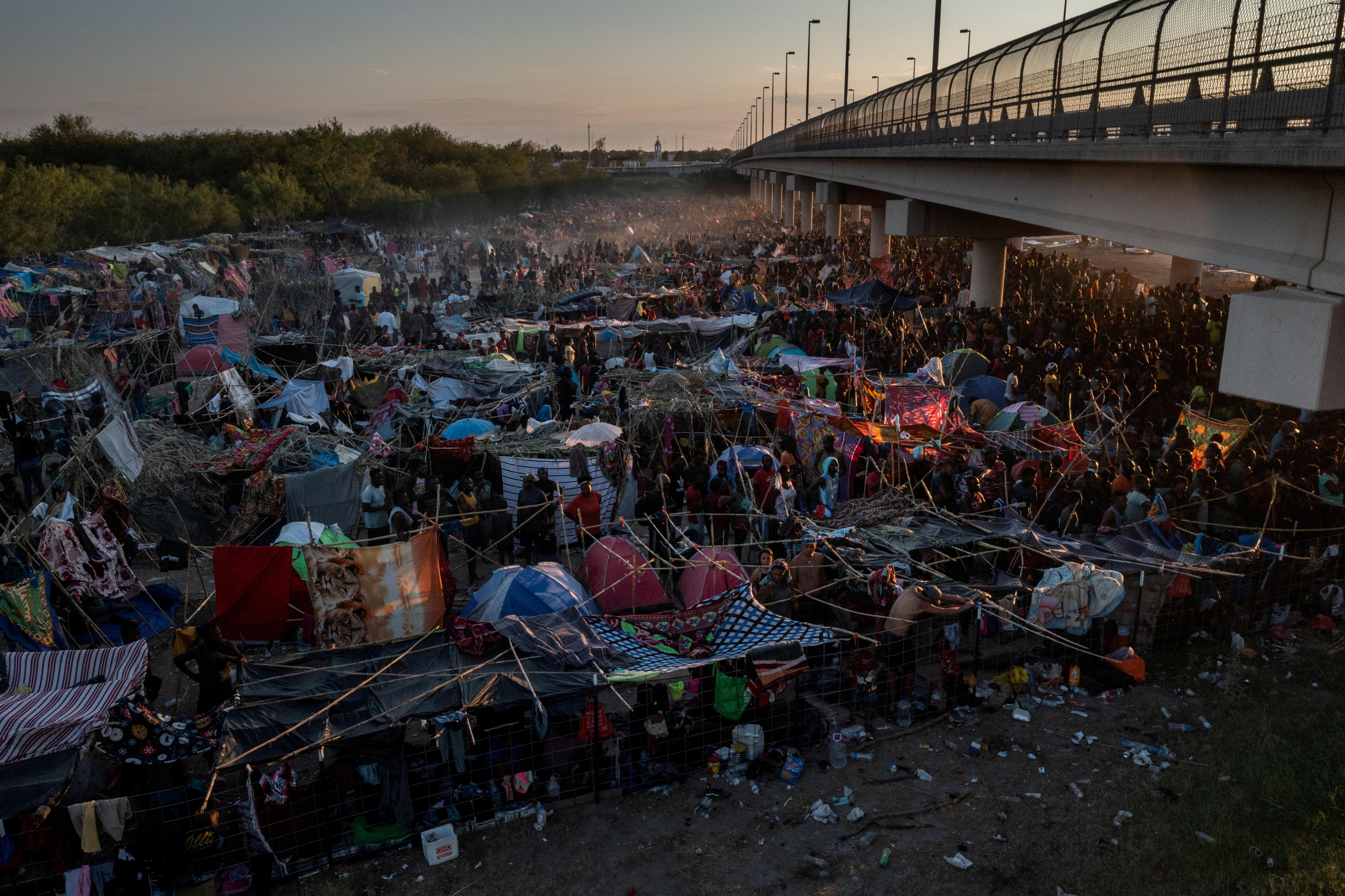 Migrants take shelter along the Del Rio International Bridge at sunset as they await to be processed after crossing the Rio Grande river into the U.S. from Ciudad Acuna in Del Rio, Texas, U.S. September 19, 2021. Picture taken with a drone. REUTERS/Adrees Latif     TPX IMAGES OF THE DAY/File Photo