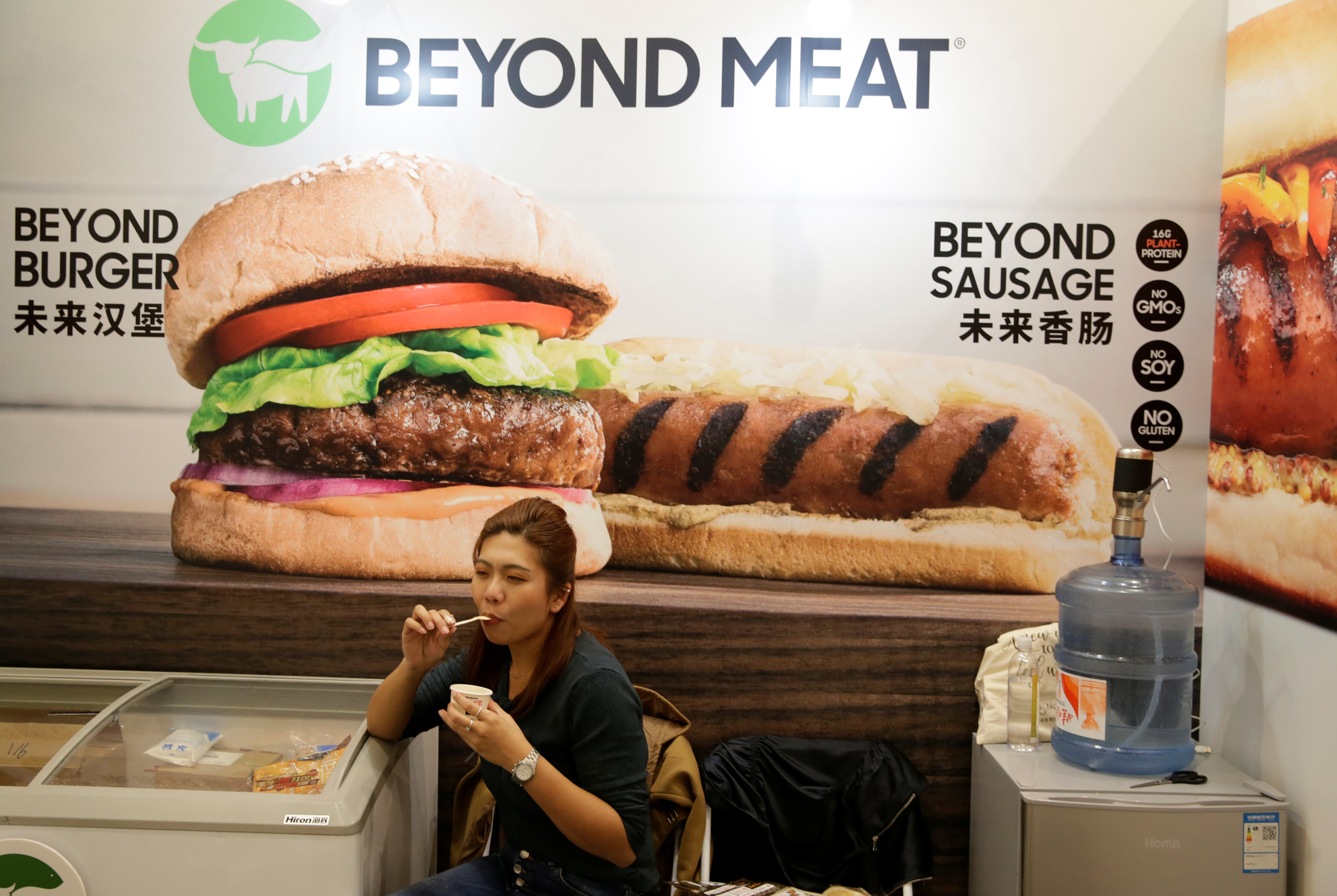 A woman sits next to a poster at the booth of plant-based food company Beyond Meat at VeggieWorld fair in Beijing, China November 8, 2019.  REUTERS/Jason Lee