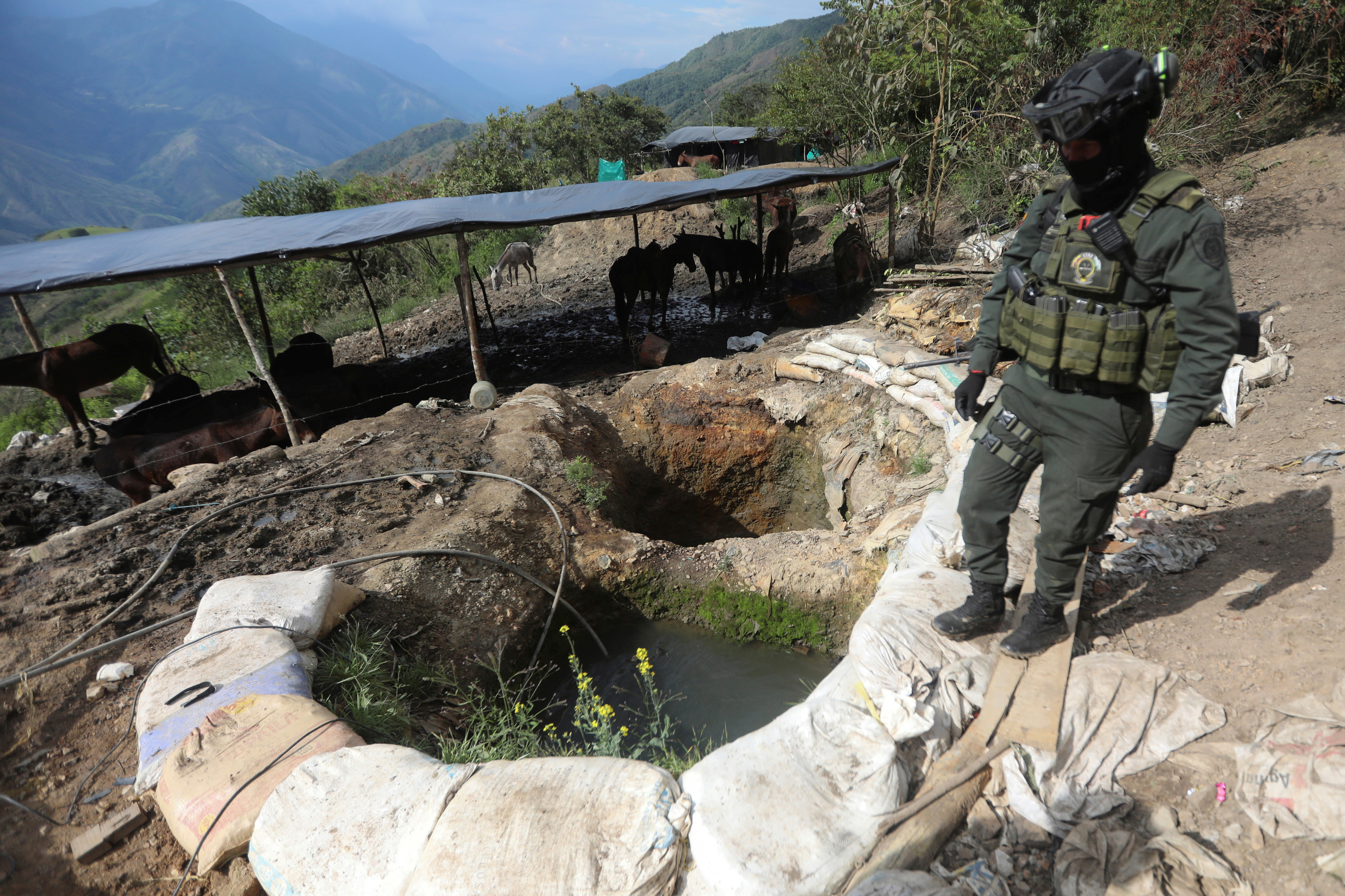 A policeman stands next to a well where minerals taken from illegal gold mines are washed in Buritica, Colombia April 20, 2021. Picture taken April 20, 2021. REUTERS/Luisa Gonzalez