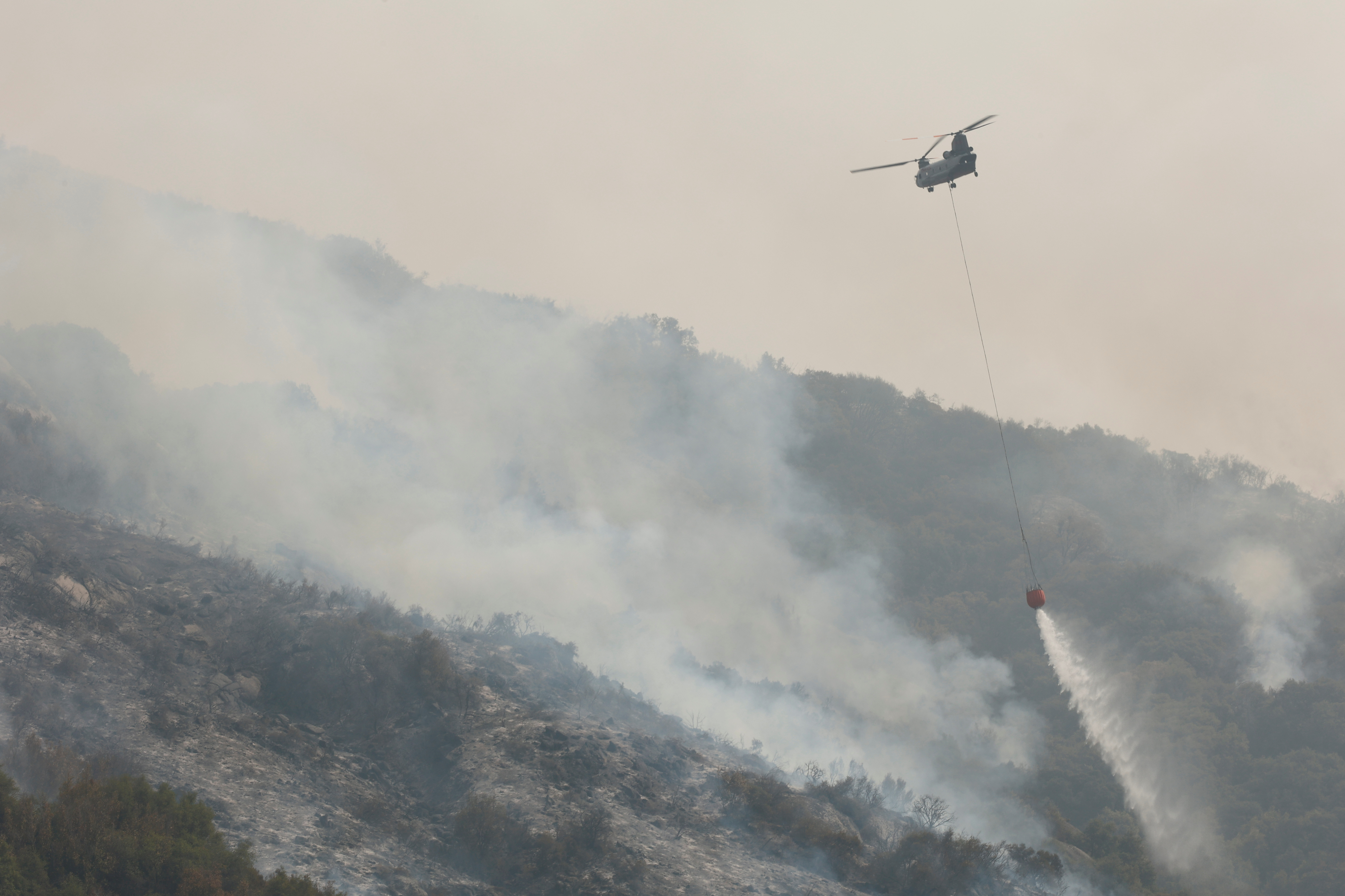 A firefighting helicopter drops water on hotspots burning in the KNP Complex fire, at Sequoia National Park in Tulare County, California, U.S. September 18, 2021. REUTERS/Fred Greaves