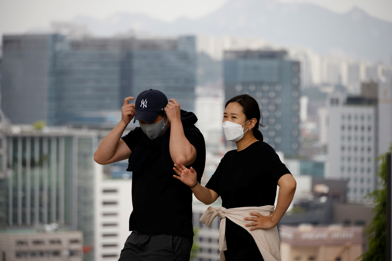 couple wearing masks to avoid contracting the coronavirus disease (COVID-19) take a walk at a park in Seoul, South Korea, May 26, 2021. REUTERS/Kim Hong-Ji