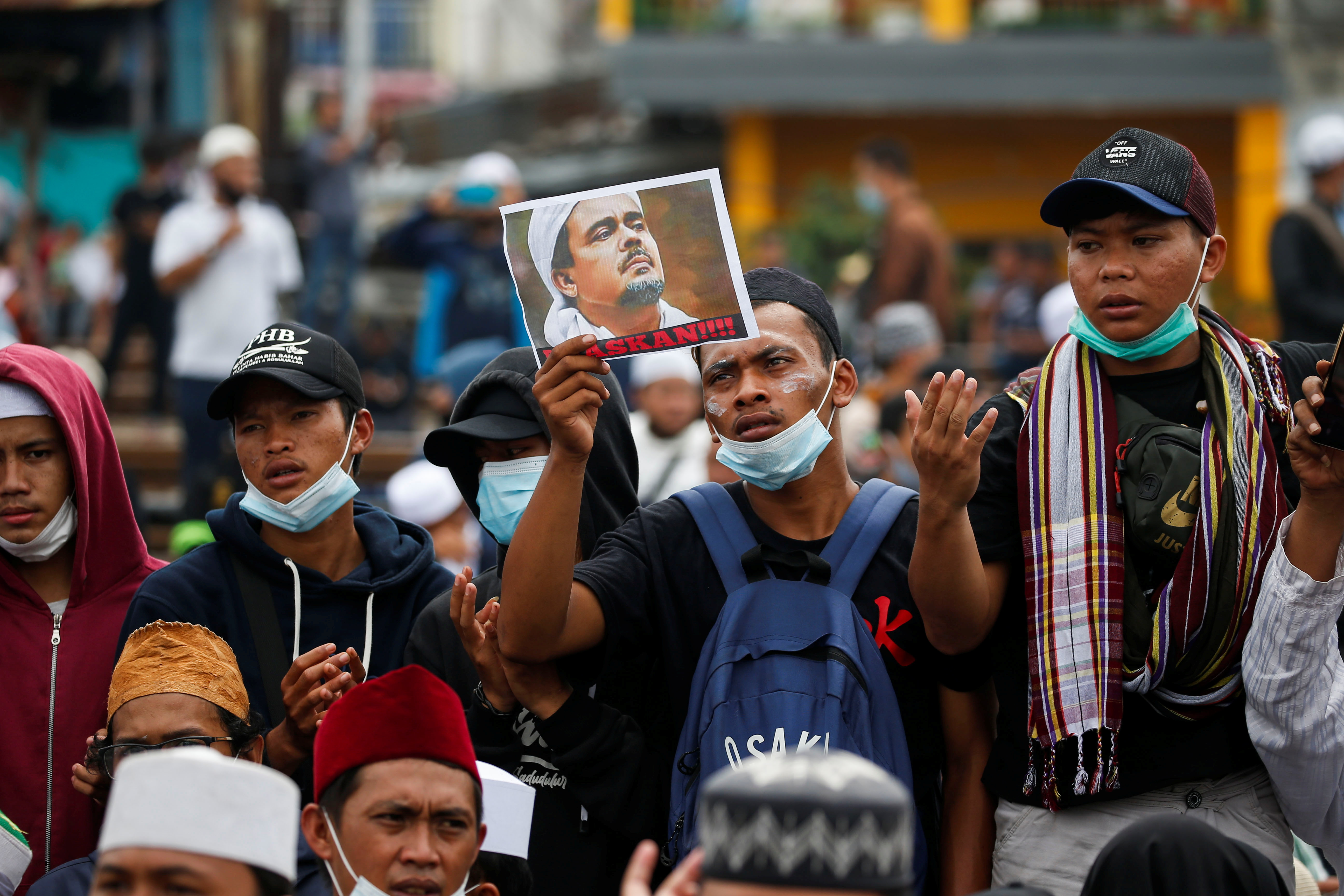A demonstrator holds a picture of Rizieq Shihab, an Indonesian Islamic cleric who is sentenced for breaching coronavirus disease (COVID-19) curbs after his return last year from self-imposed exile, during a protest supporting him, in Jakarta, Indonesia, June 24, 2021. REUTERS/Willy Kurniawan
