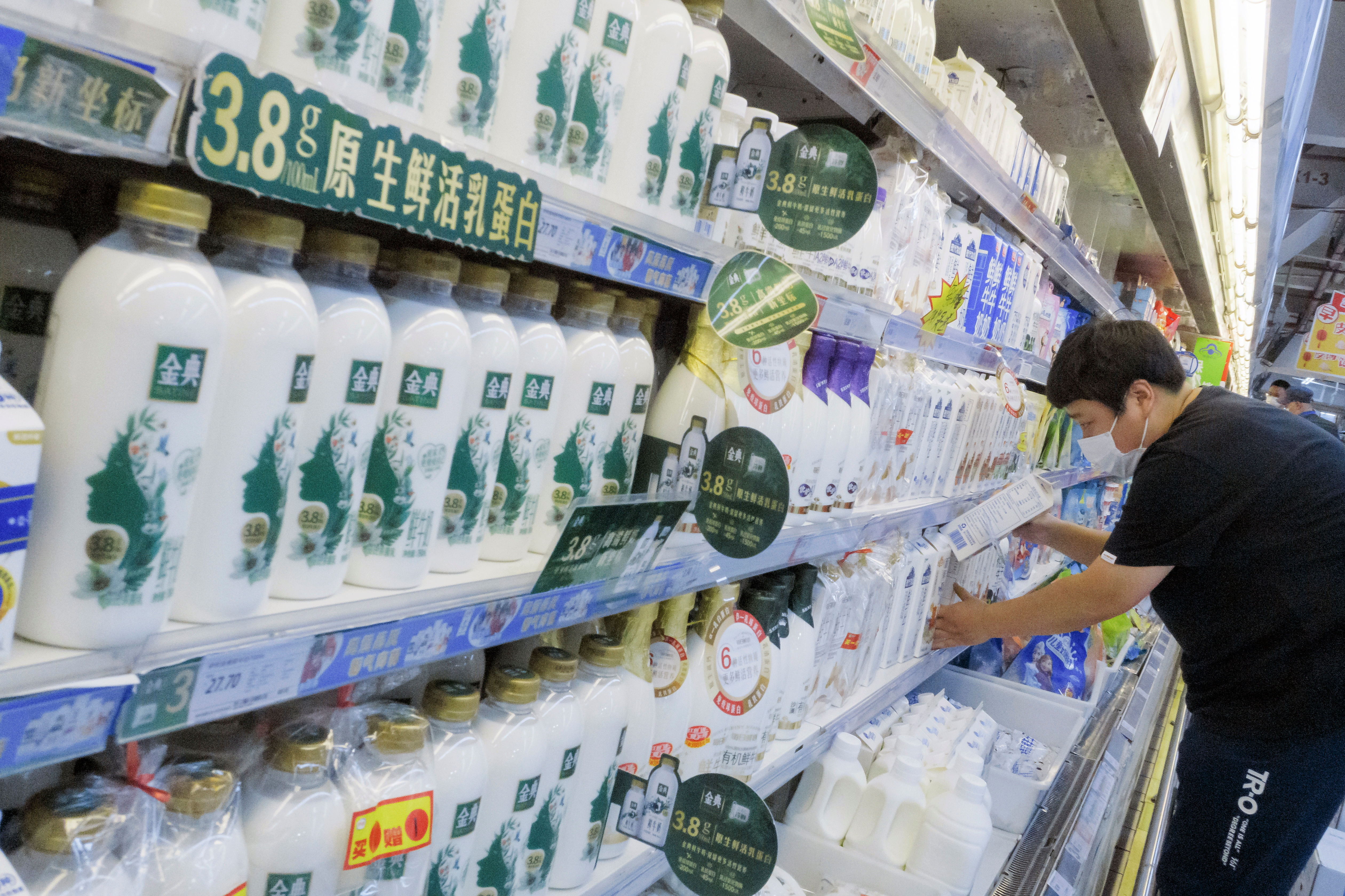A staff member places cartons of milk on refrigerator shelves at a supermarket in Beijing, China, May 21, 2021. REUTERS/Thomas Peter