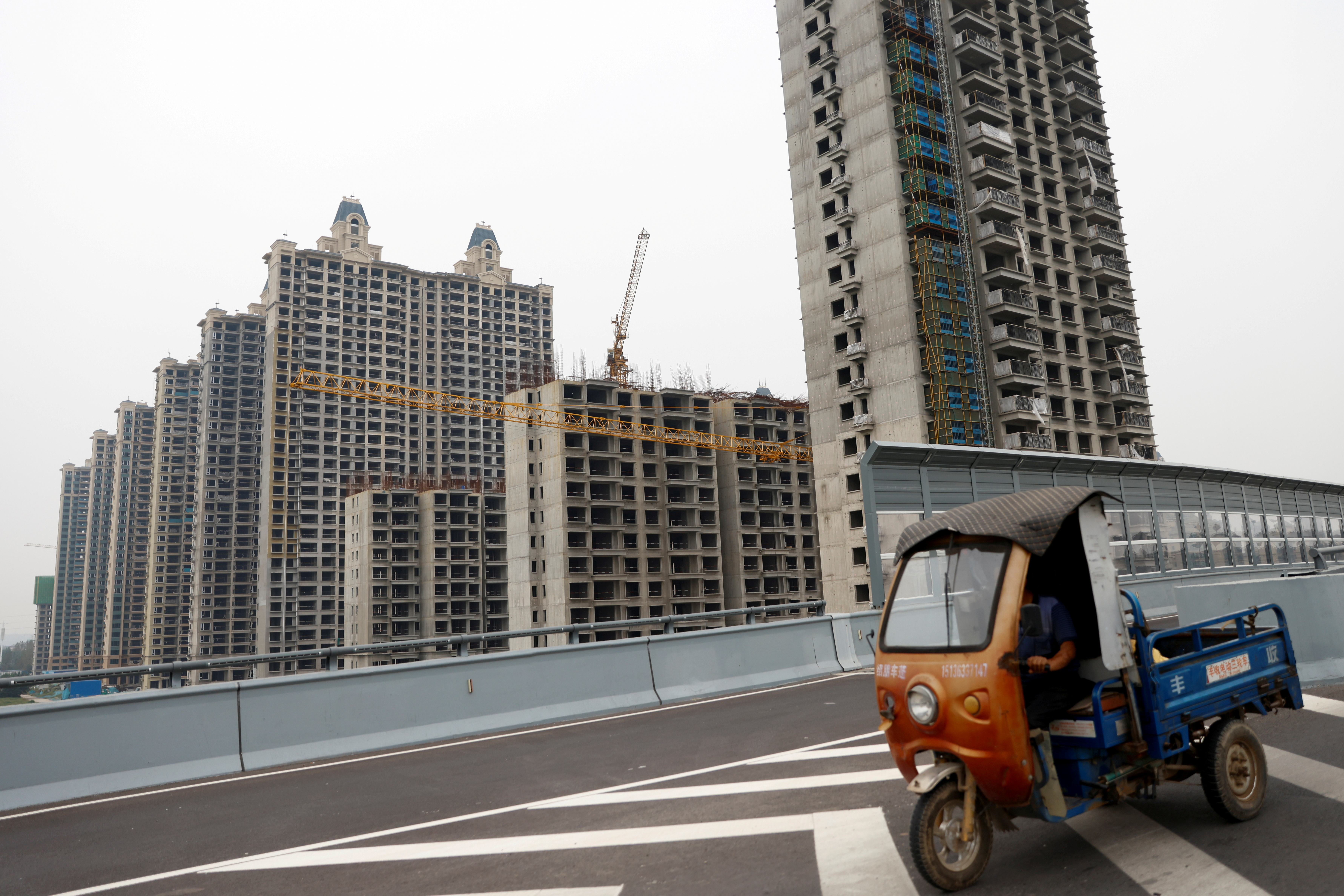 A vehicle drives past unfinished residential buildings at Evergrande Oasis, a housing complex developed by Evergrande Group, in Luoyang, China September 16, 2021. REUTERS/Carlos Garcia Rawlins/File Photo