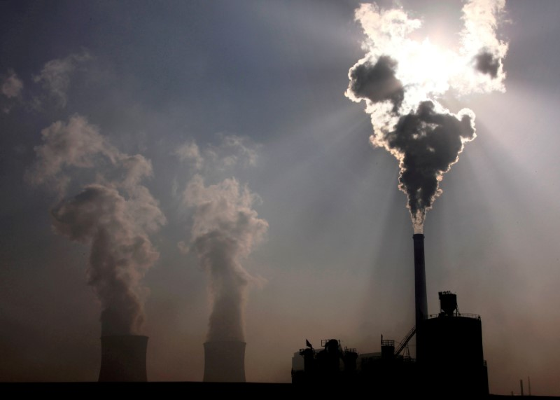 A coal-burning power plant can be seen behind a factory in the city of Baotou, in China's Inner Mongolia Autonomous Region, October 31, 2010.  REUTERS/David Gray