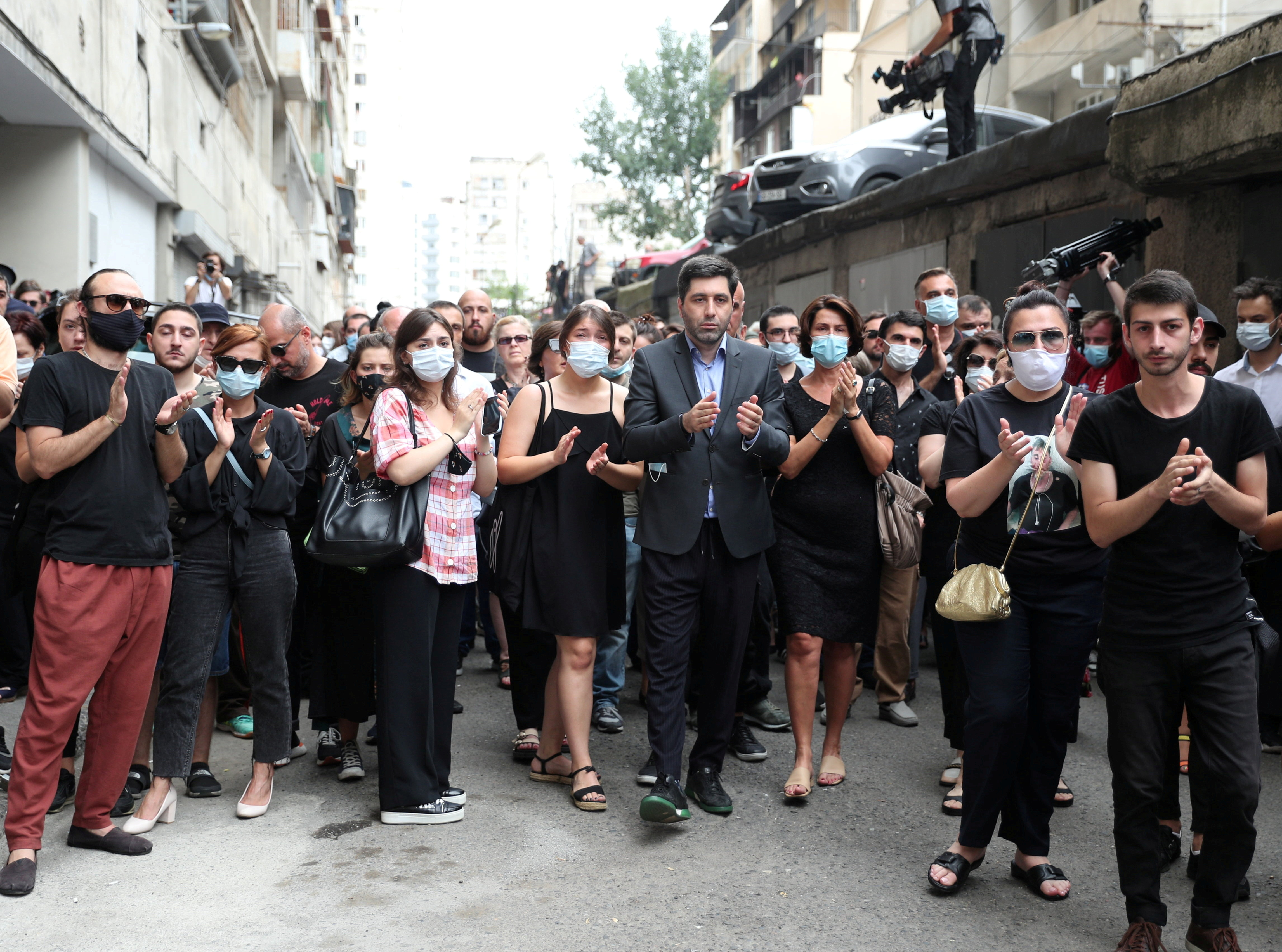 Mourners applaud during a funeral of journalist Alexander Lashkarava in Tbilisi, Georgia July 13, 2021. Lashkarava was found dead at his home several days after he was beaten during attacks on LGBT+ activists in Tbilisi. REUTERS/Irakli Gedenidze/File Photo