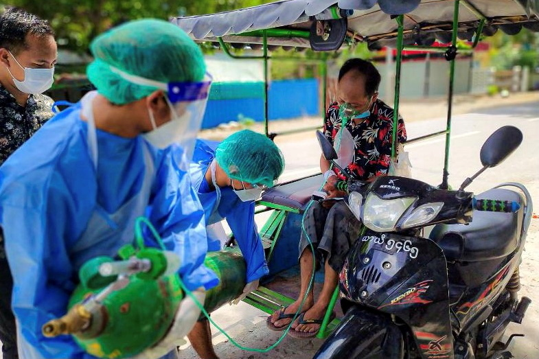 Volunteers help provide a coronavirus  (COVID-19) patient with extra oxygen in the town of Kale, Sagaing Region, Myanmar, July 5, 2021.  REUTERS/Stringer/File Photo