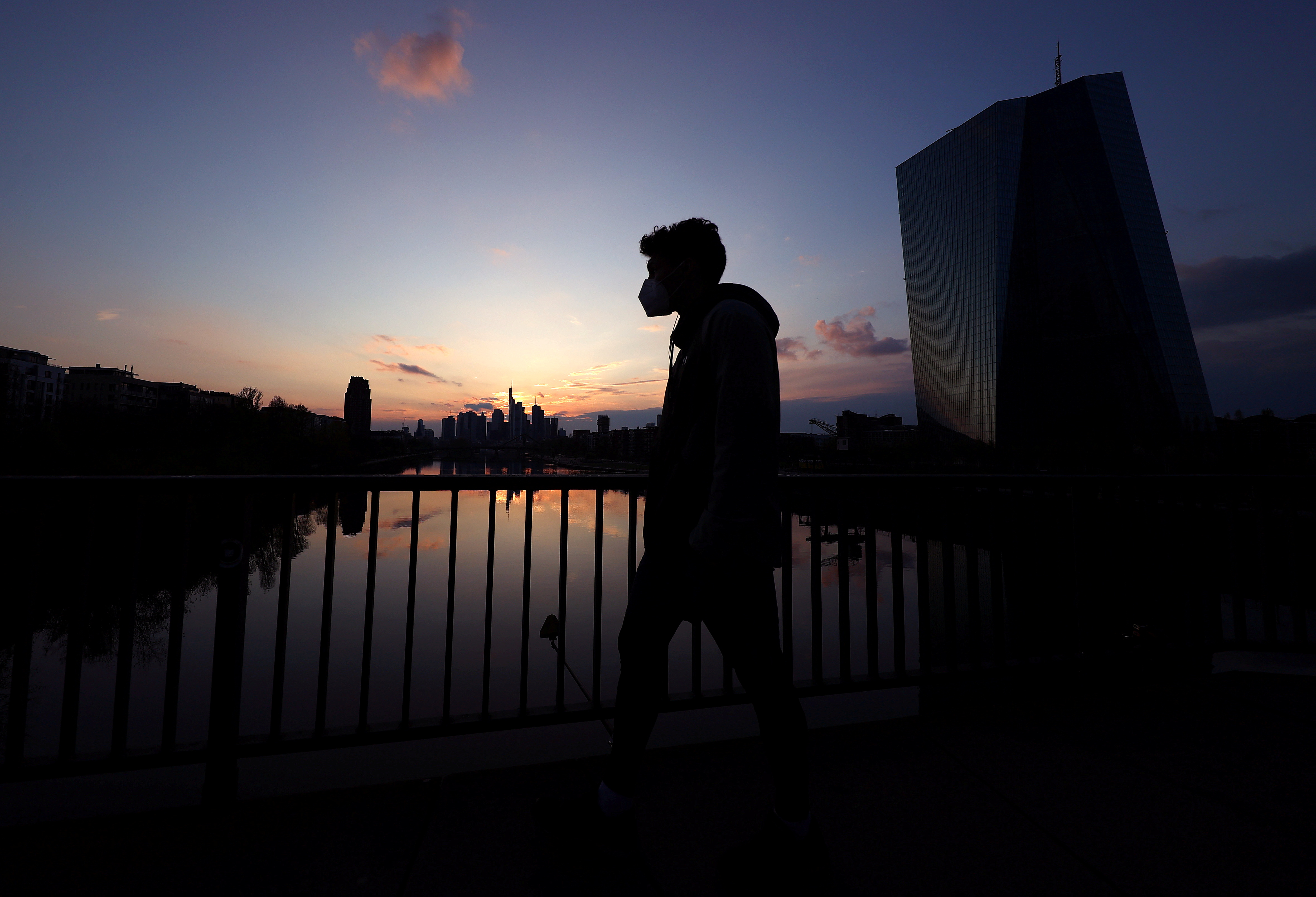 A man wearing a protective mask walks past the European Central Bank (ECB) during sunset as the spread of the coronavirus disease (COVID-19) continues in Frankfurt, Germany, April 18, 2021.  REUTERS/Kai Pfaffenbach
