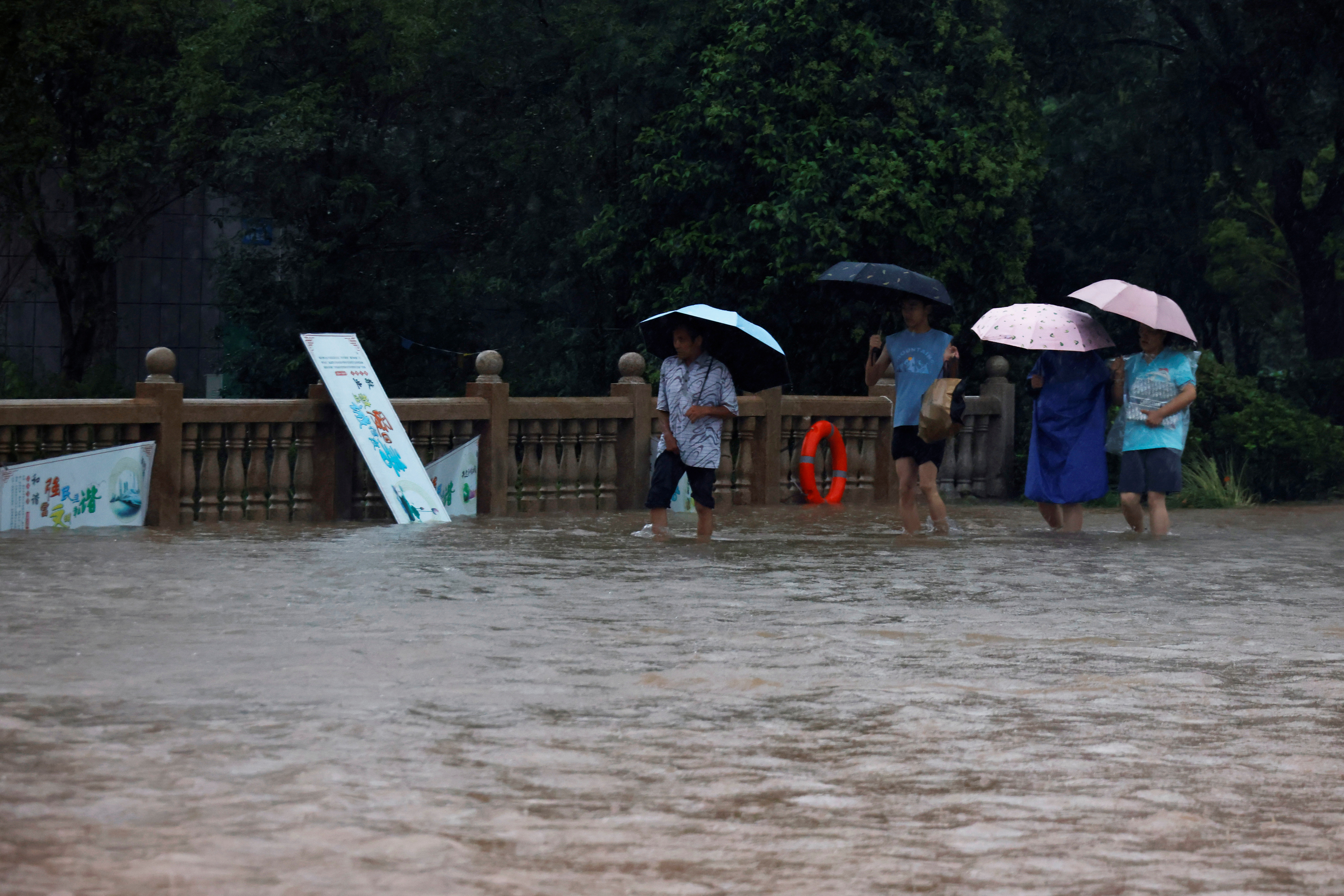 People holding umbrellas amid heavy rainfall wade through floodwaters on a bridge in Hebi, Henan province, China July 22, 2021. REUTERS/Aly Song
